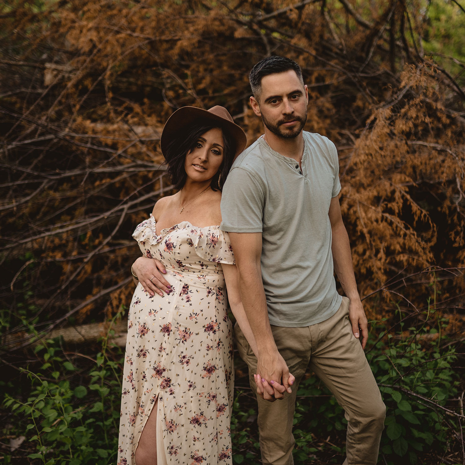 pregnant-wife-and-husband-standing-back-to-back-holding-hands-looking-at-camera-maternity-desmoines-iowa-raelyn-ramey-photography.jpg