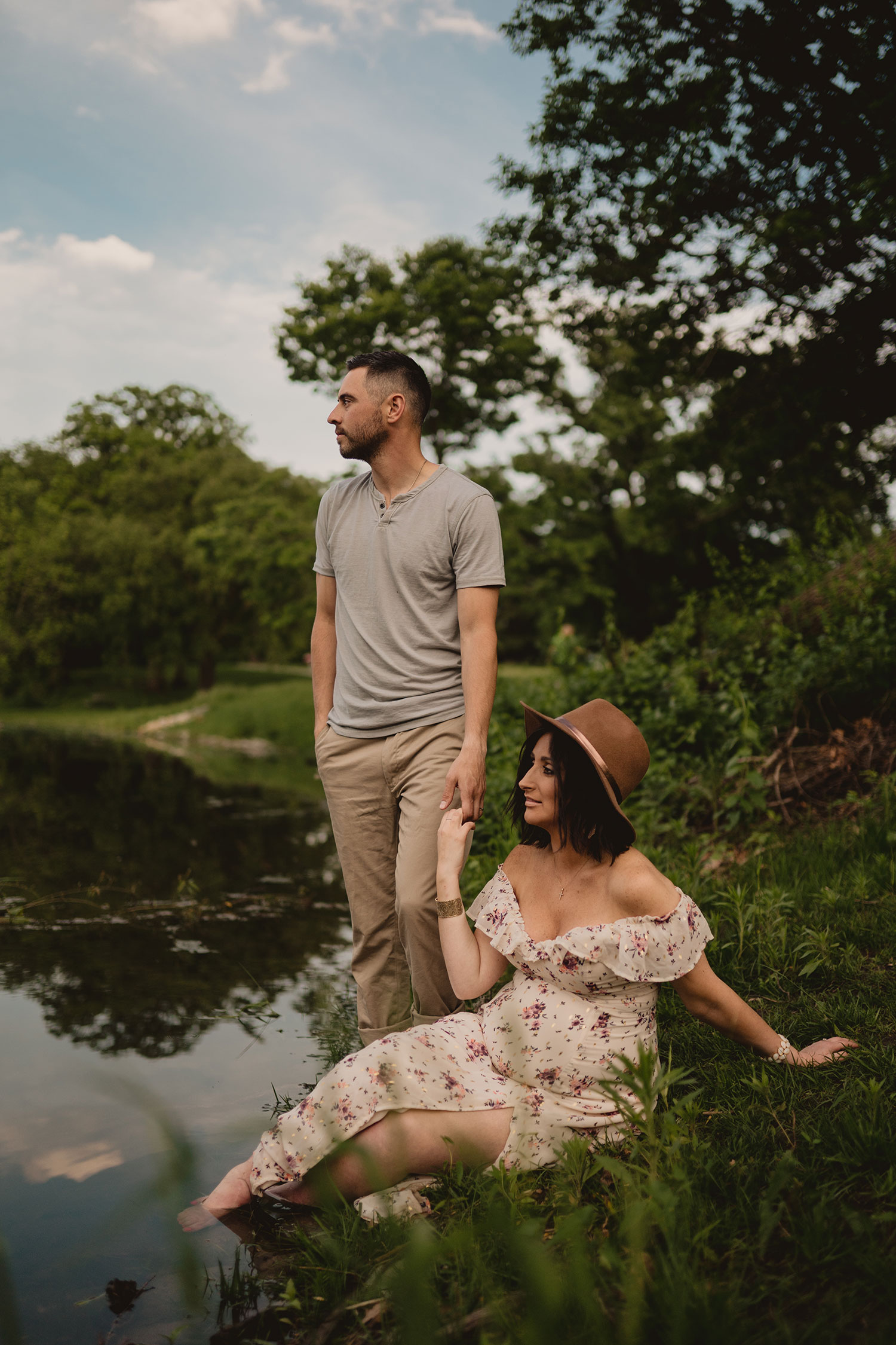 pregnant-woman-sitting-by-water-hilding-husbands-hand-maternity-desmoines-iowa-raelyn-ramey-photography.jpg
