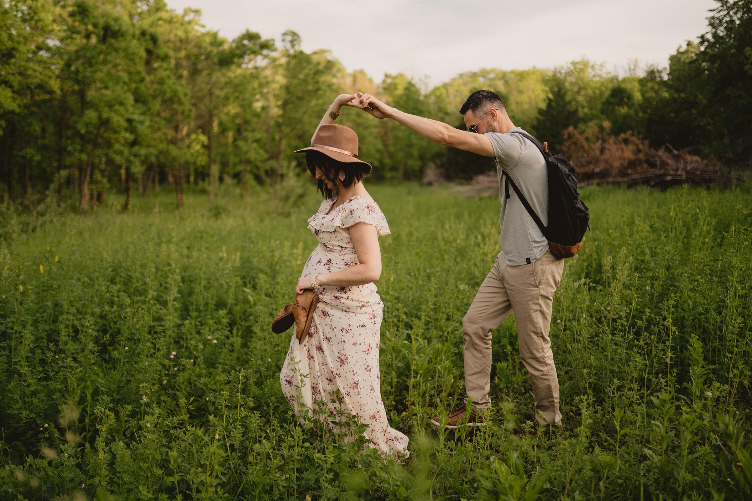 pregnant-woman-and-husband-walking-through-tall-grass-maternity-desmoines-iowa-raelyn-ramey-photography.jpg