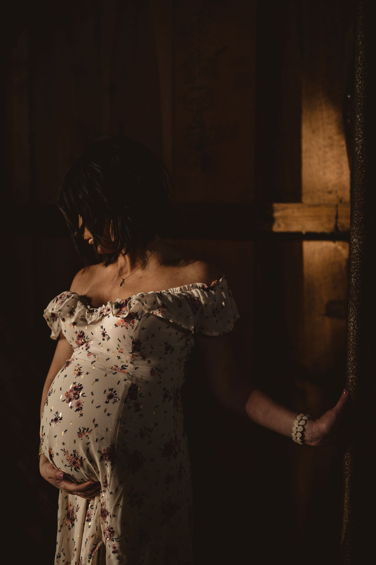 pregnant-woman-standing-in-moody-light-maternity-desmoines-iowa-raelyn-ramey-photography.jpg