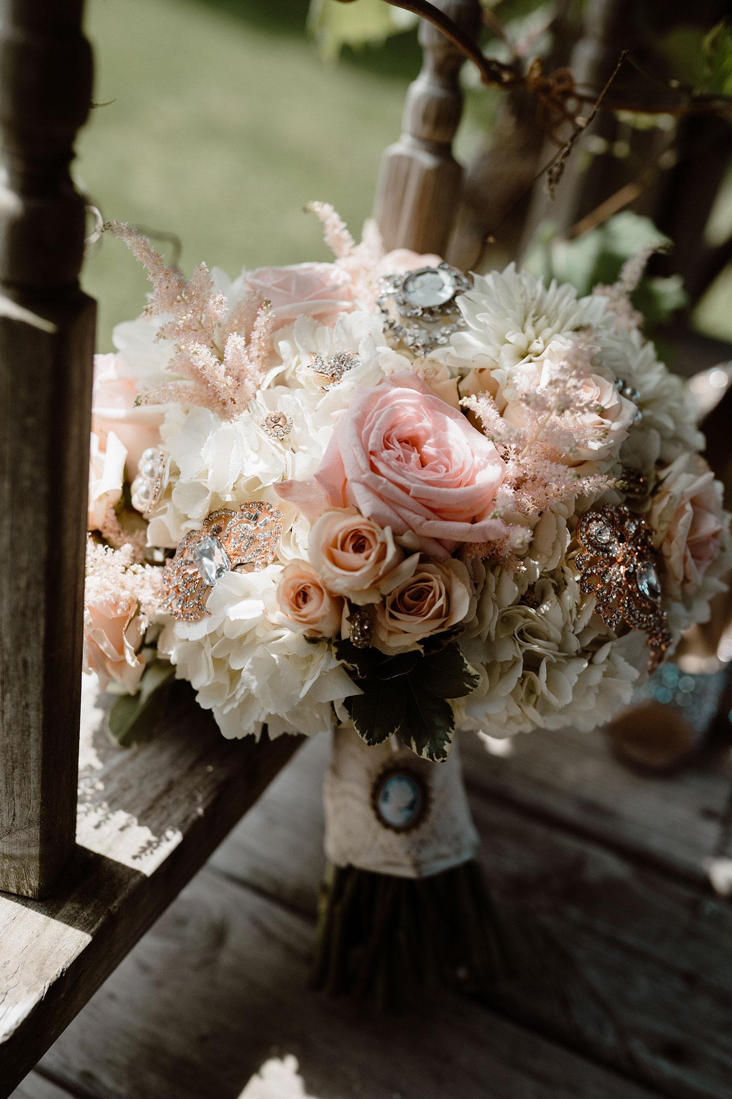 flower-bouquet-sitting-against-deck-detail-shot-wedding-summerset-winery-indianola-iowa-raelyn-ramey-photography.jpg