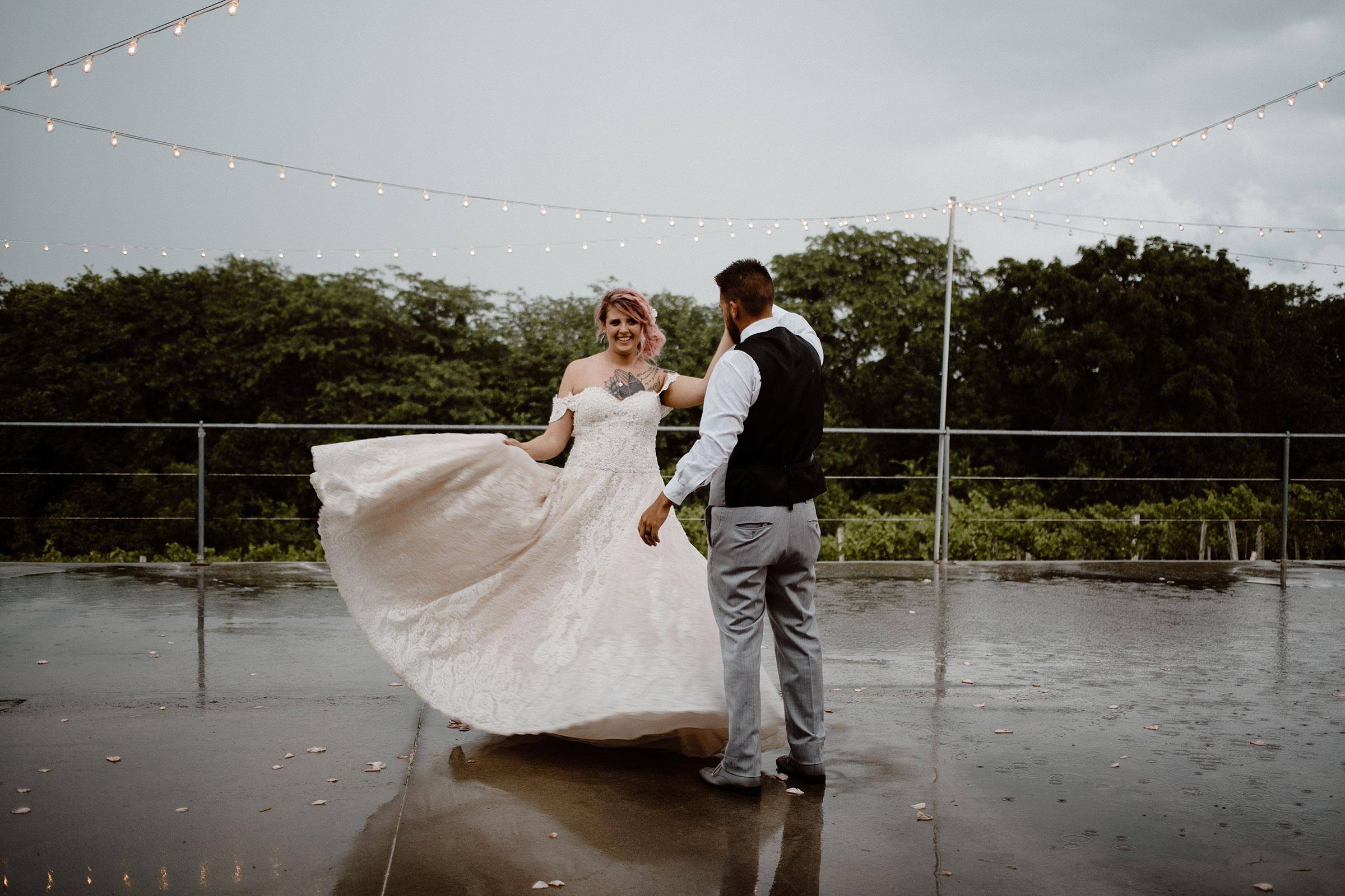 bgroom-spinning-bride-in-rain-puddles-wedding-summerset-winery-indianola-iowa-raelyn-ramey-photography.jpg