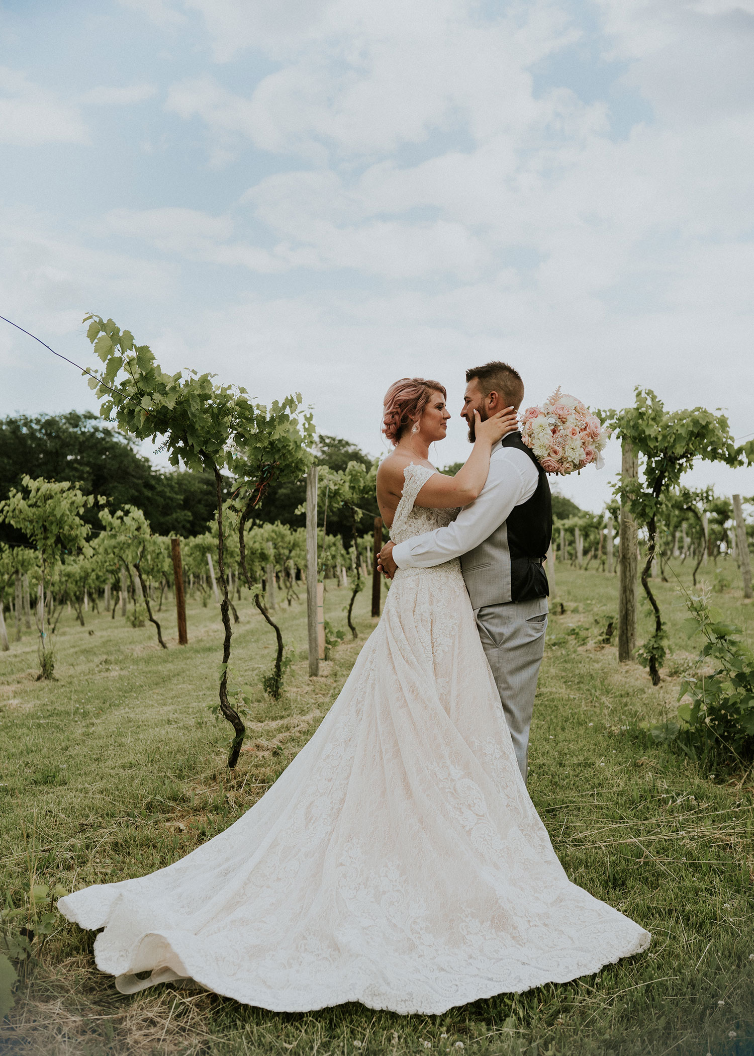 bride-and-groom-looking-at-each-other-in-vineyard-wedding-summerset-winery-indianola-iowa-raelyn-ramey-photography.jpg