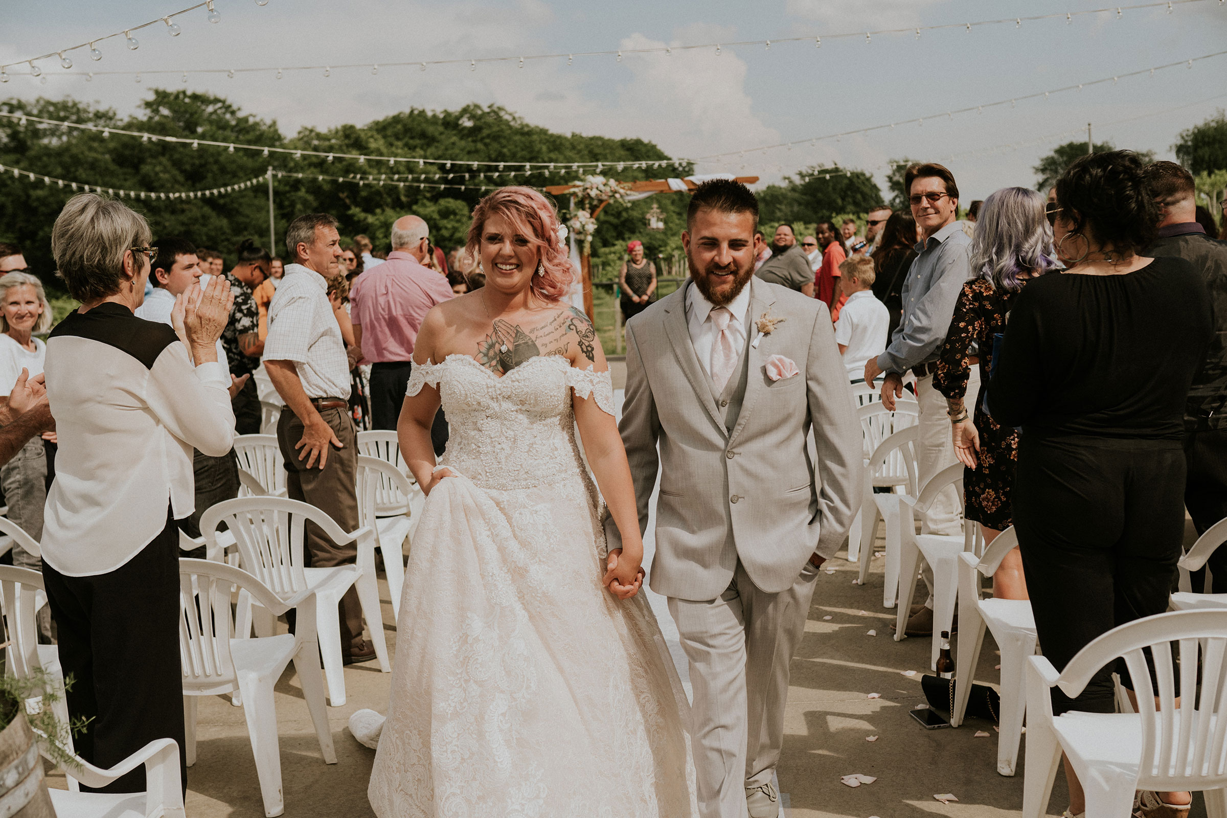 bride-and-groom-walking-back-out-of-aisle-wedding-summerset-winery-indianola-iowa-raelyn-ramey-photography.jpg