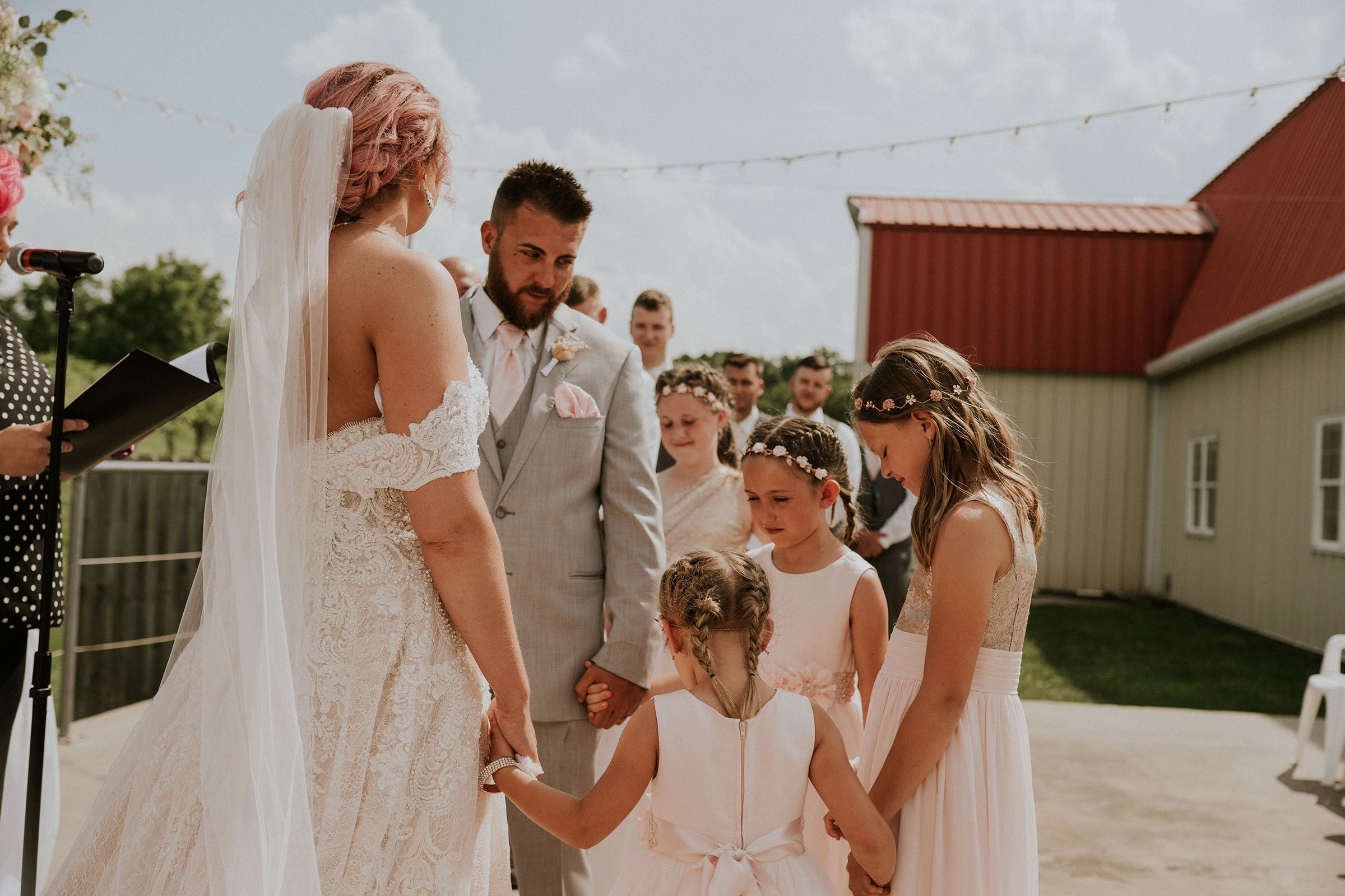 bride-groom-and-daughters-holding-hands-during-ceremony-wedding-summerset-winery-indianola-iowa-raelyn-ramey-photography.jpg