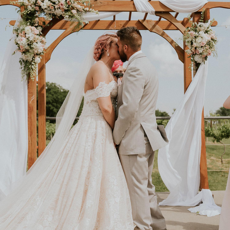 bride-groom-ceremony-kiss-wedding-summerset-winery-indianola-iowa-raelyn-ramey-photography.jpg