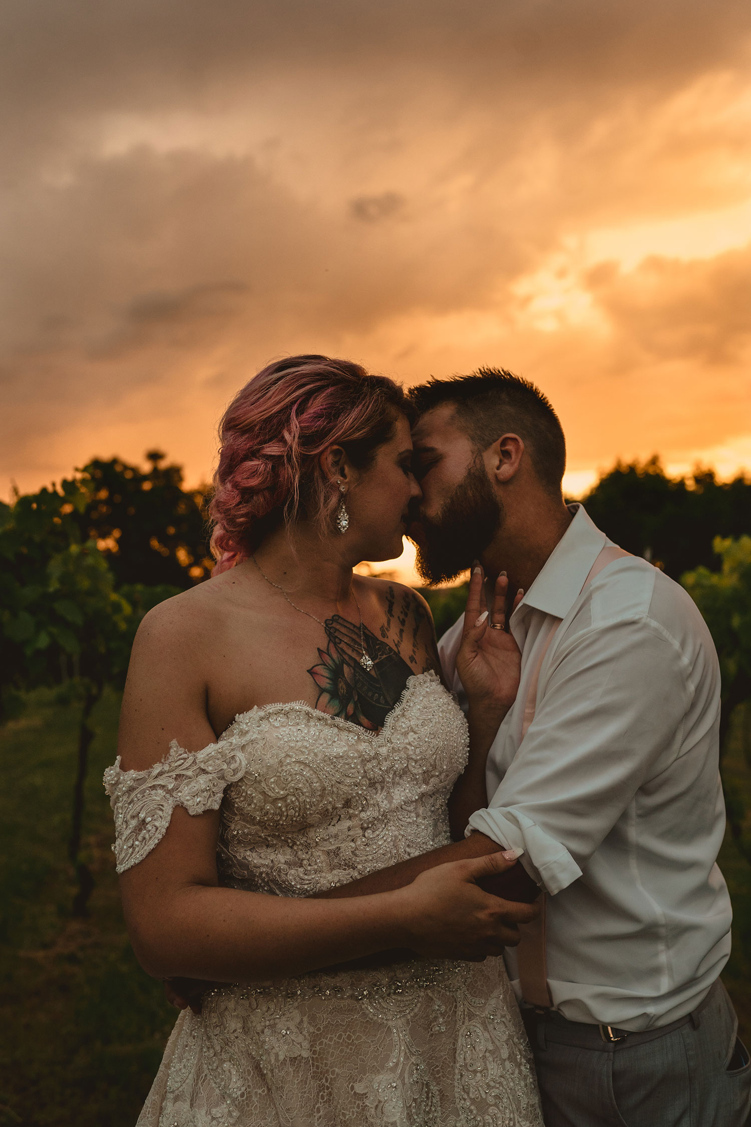 bride-groom-kissing-at-sunset-with-dark-clouds-in-vineyard-wedding-summerset-winery-indianola-iowa-raelyn-ramey-photography.jpg