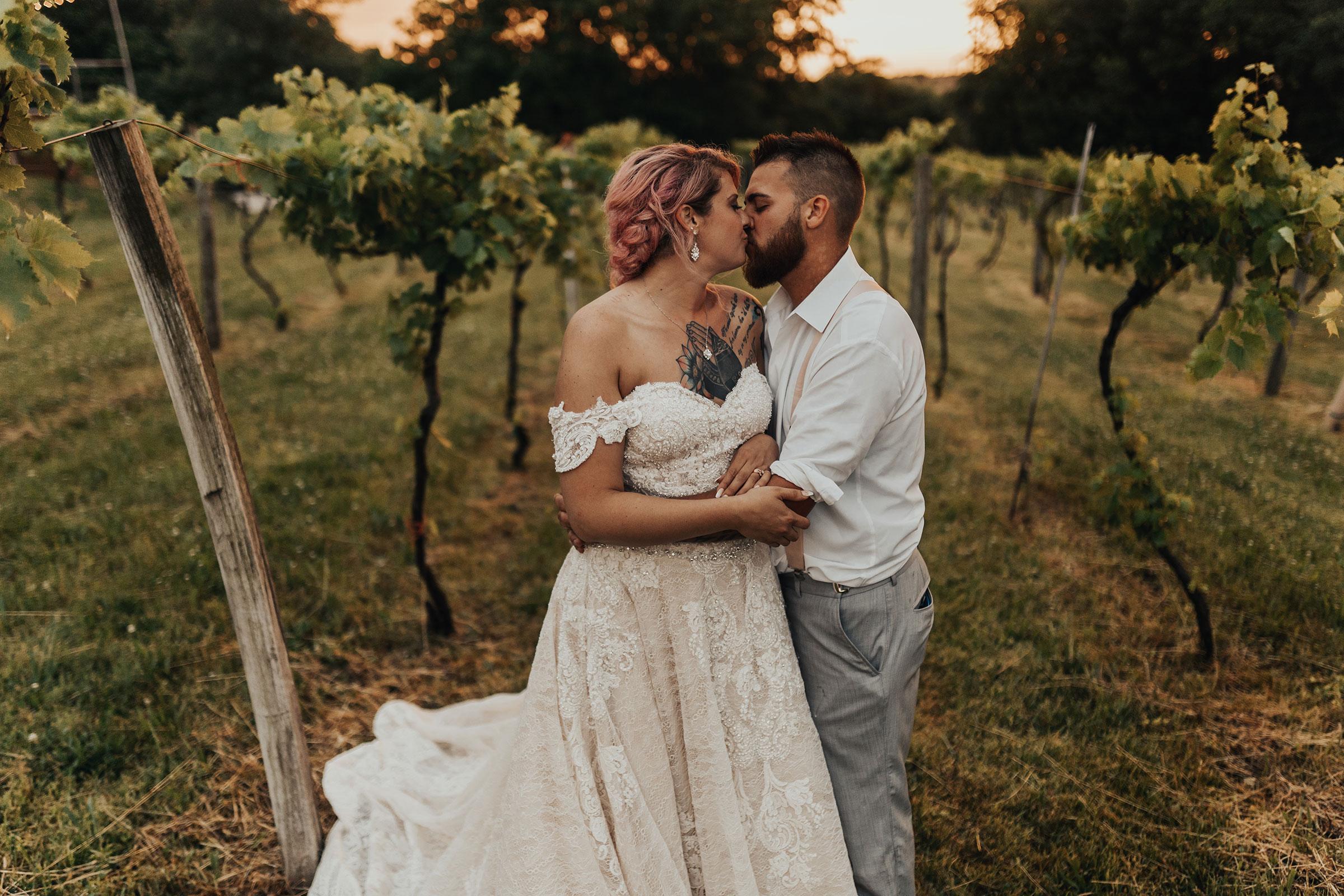 bride-groom-kissing-in-vineyard-wedding-summerset-winery-indianola-iowa-raelyn-ramey-photography.jpg