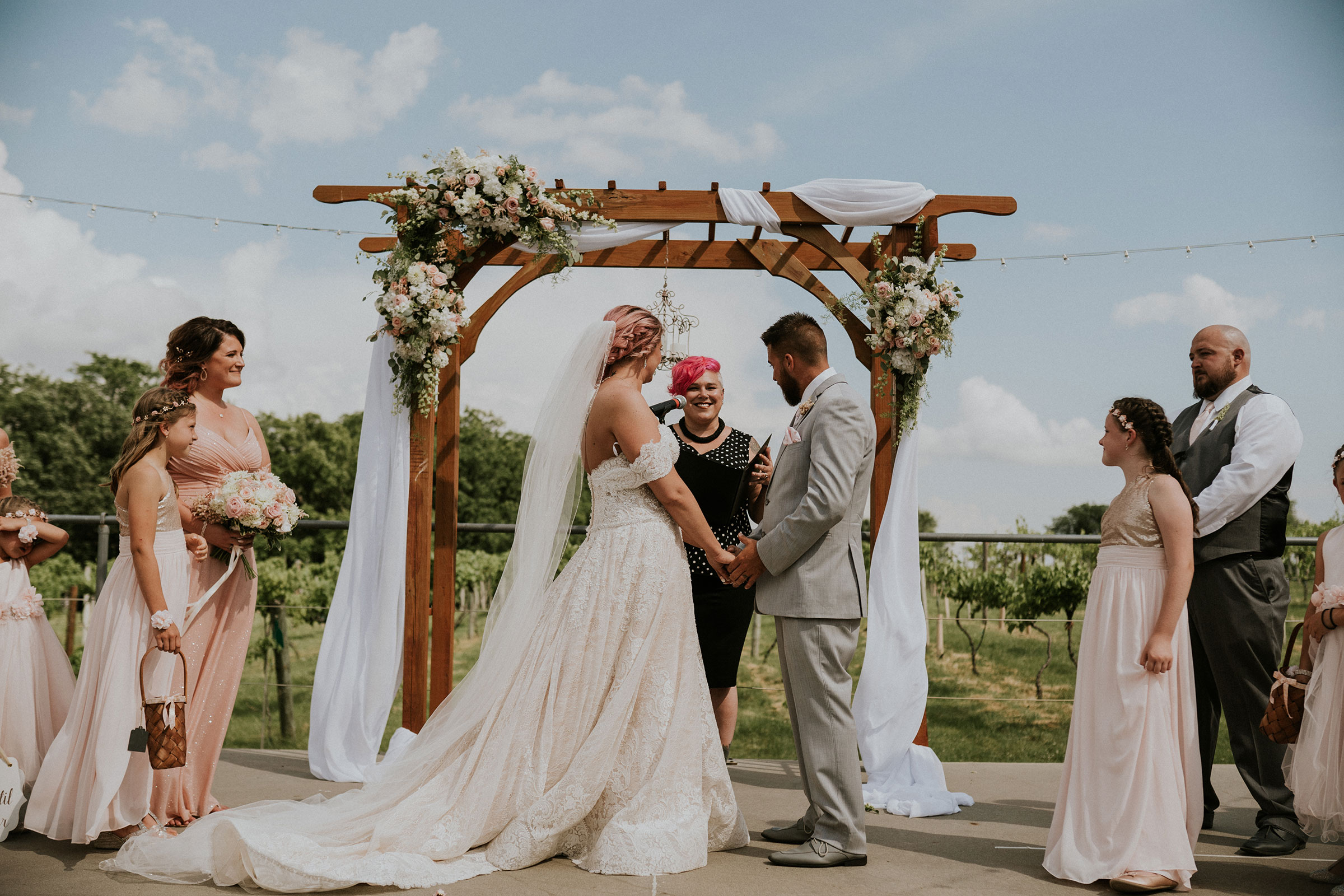 bride-groom-listening-to-officiant-wedding-summerset-winery-indianola-iowa-raelyn-ramey-photography.jpg
