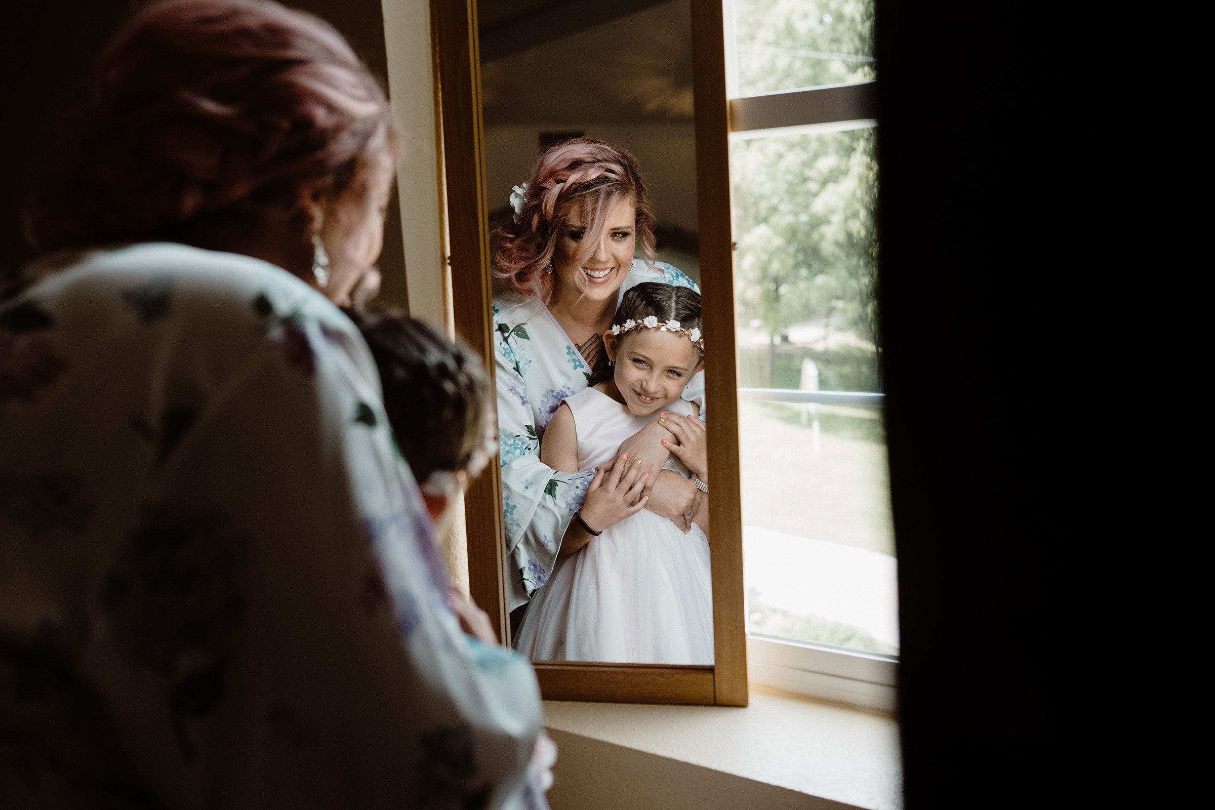 bride-holding-and-smiling-at-flower-girl-in-mirror-wedding-summerset-winery-indianola-iowa-raelyn-ramey-photography.jpg