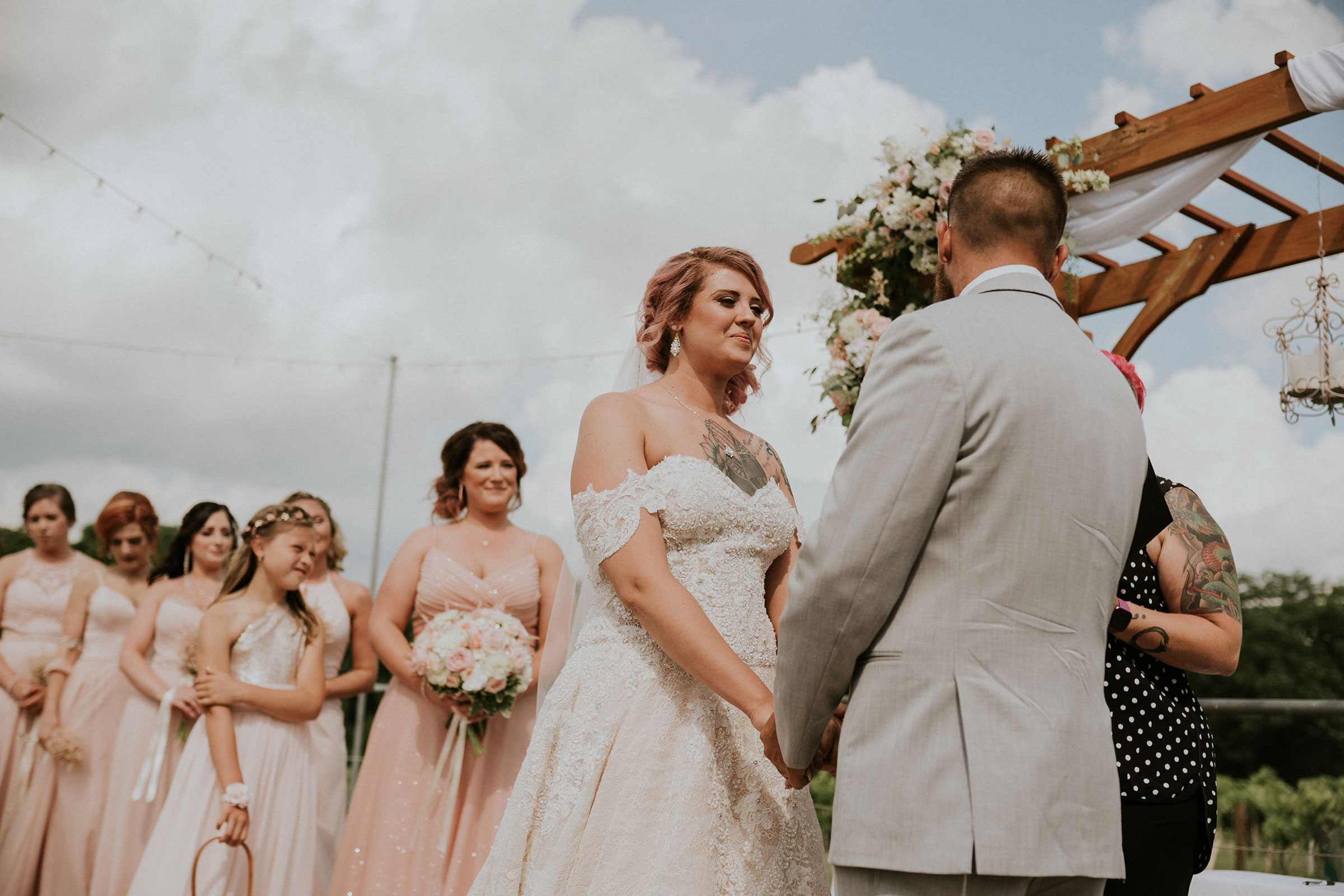 bride-holding-grooms-hand-during-ceremony-wedding-summerset-winery-indianola-iowa-raelyn-ramey-photography.jpg