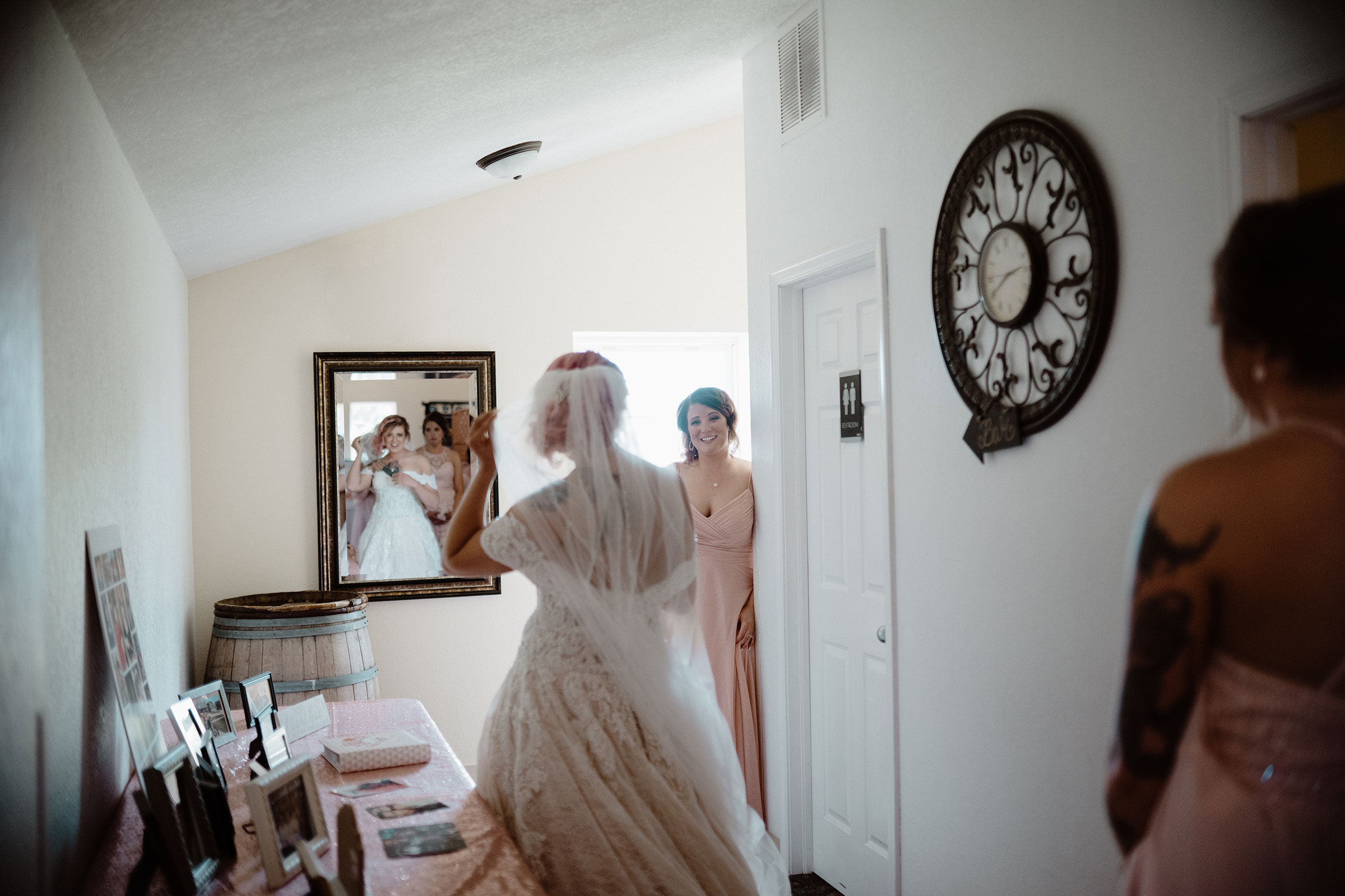 bride-looking-in-mirror-while-sister-watches-wedding-summerset-winery-indianola-iowa-raelyn-ramey-photography.jpg