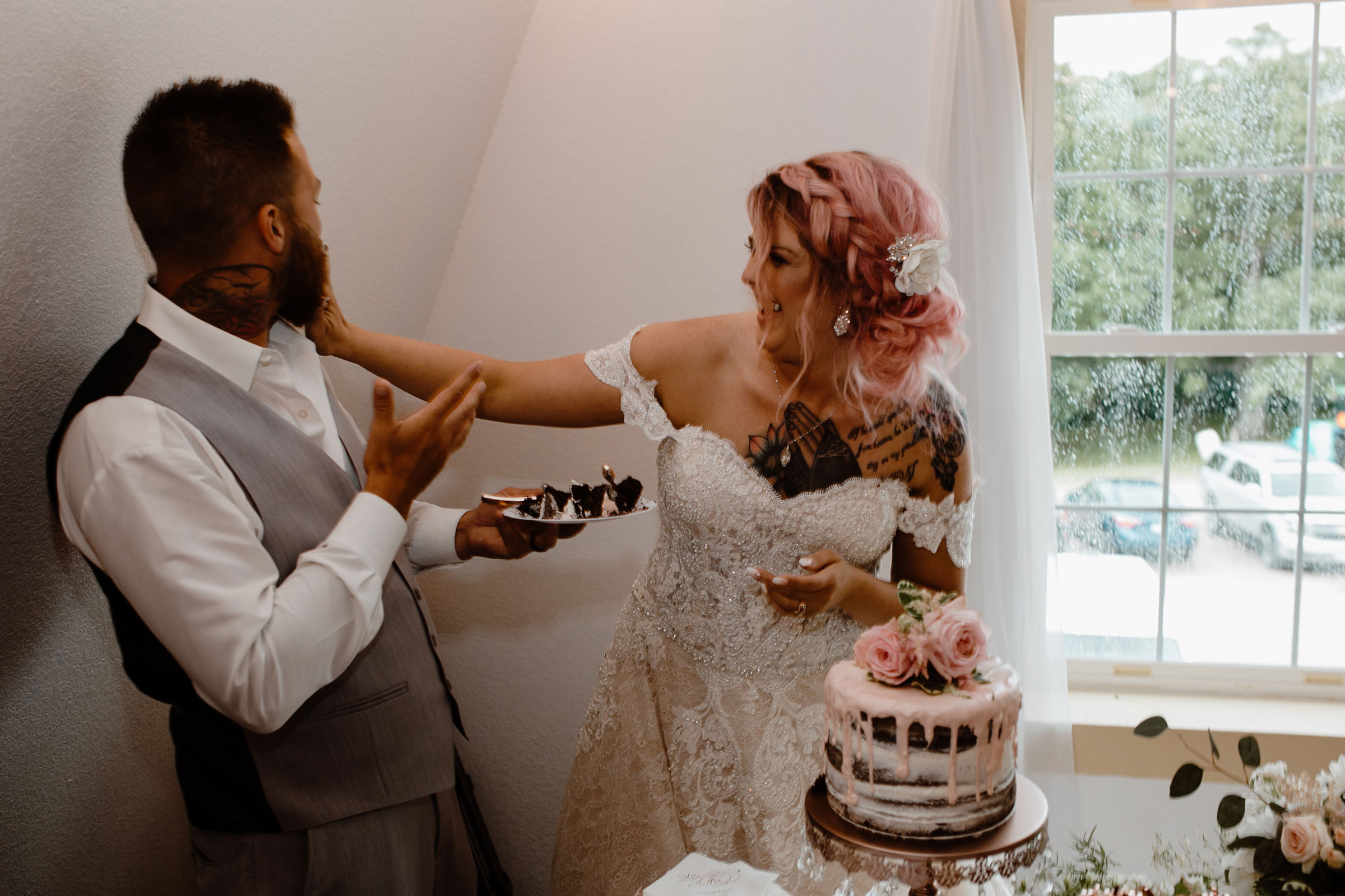 bride-shoving-cake-in-grooms-face-wedding-summerset-winery-indianola-iowa-raelyn-ramey-photography.jpg