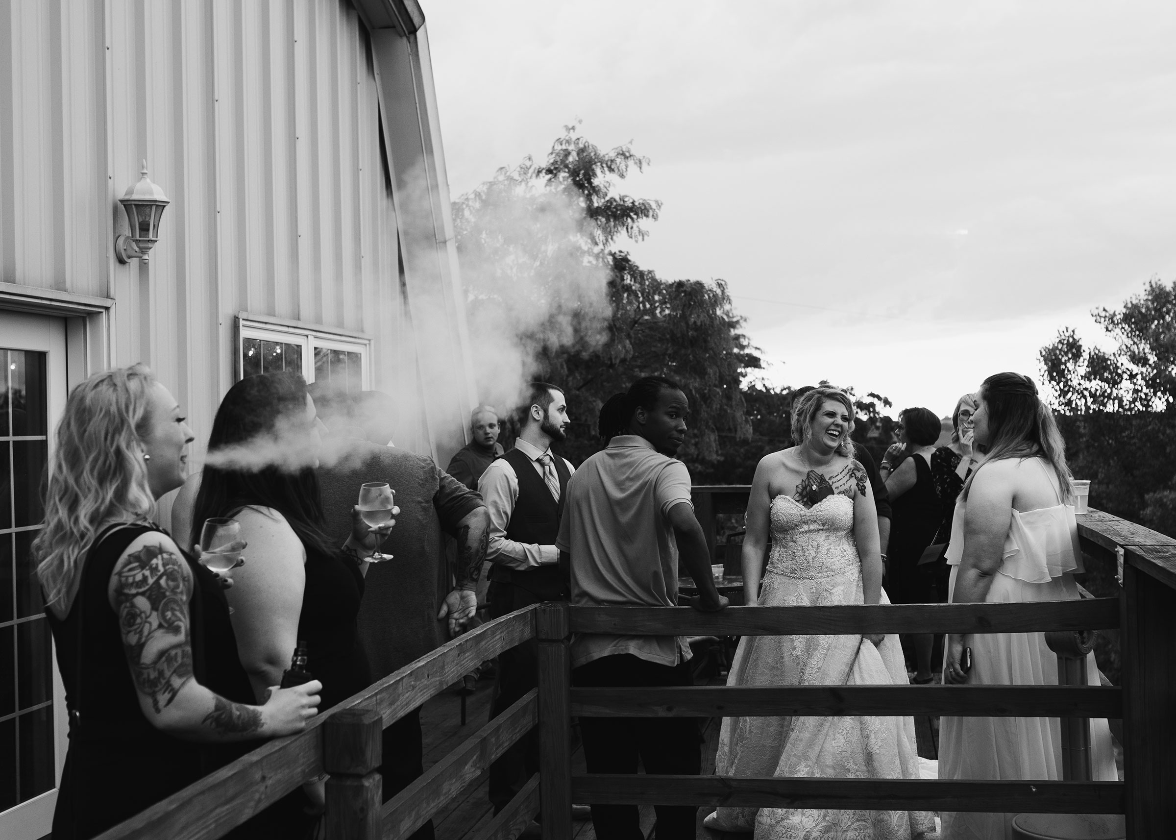 bride-standing-on-deck-of-venue-laughing-while-people-smoke-wedding-summerset-winery-indianola-iowa-raelyn-ramey-photography.jpg
