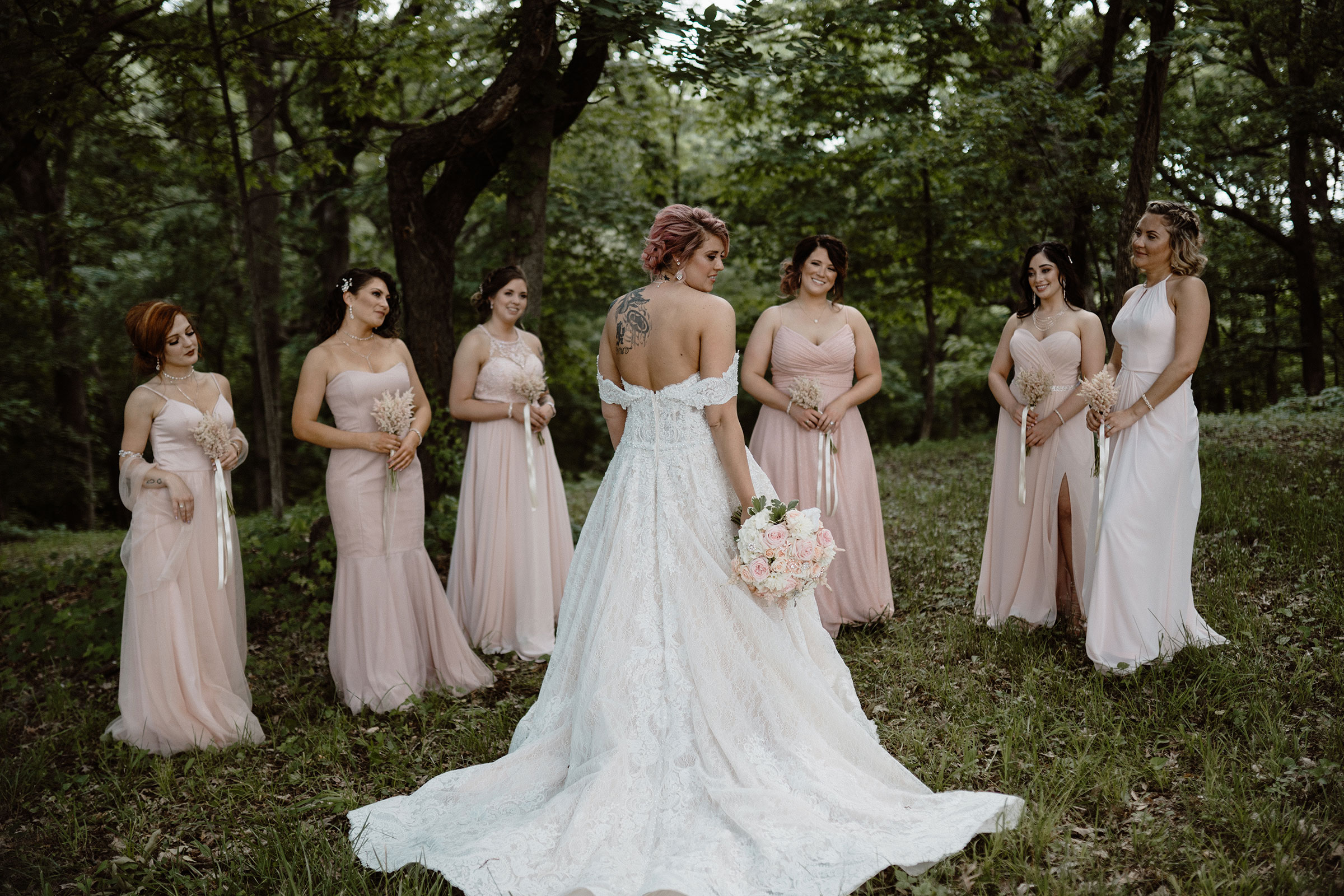 bride-standing-with-her-back-towards-camera-while-bridesmaids-stand-looking-at-her-wedding-summerset-winery-indianola-iowa-raelyn-ramey-photography.jpg