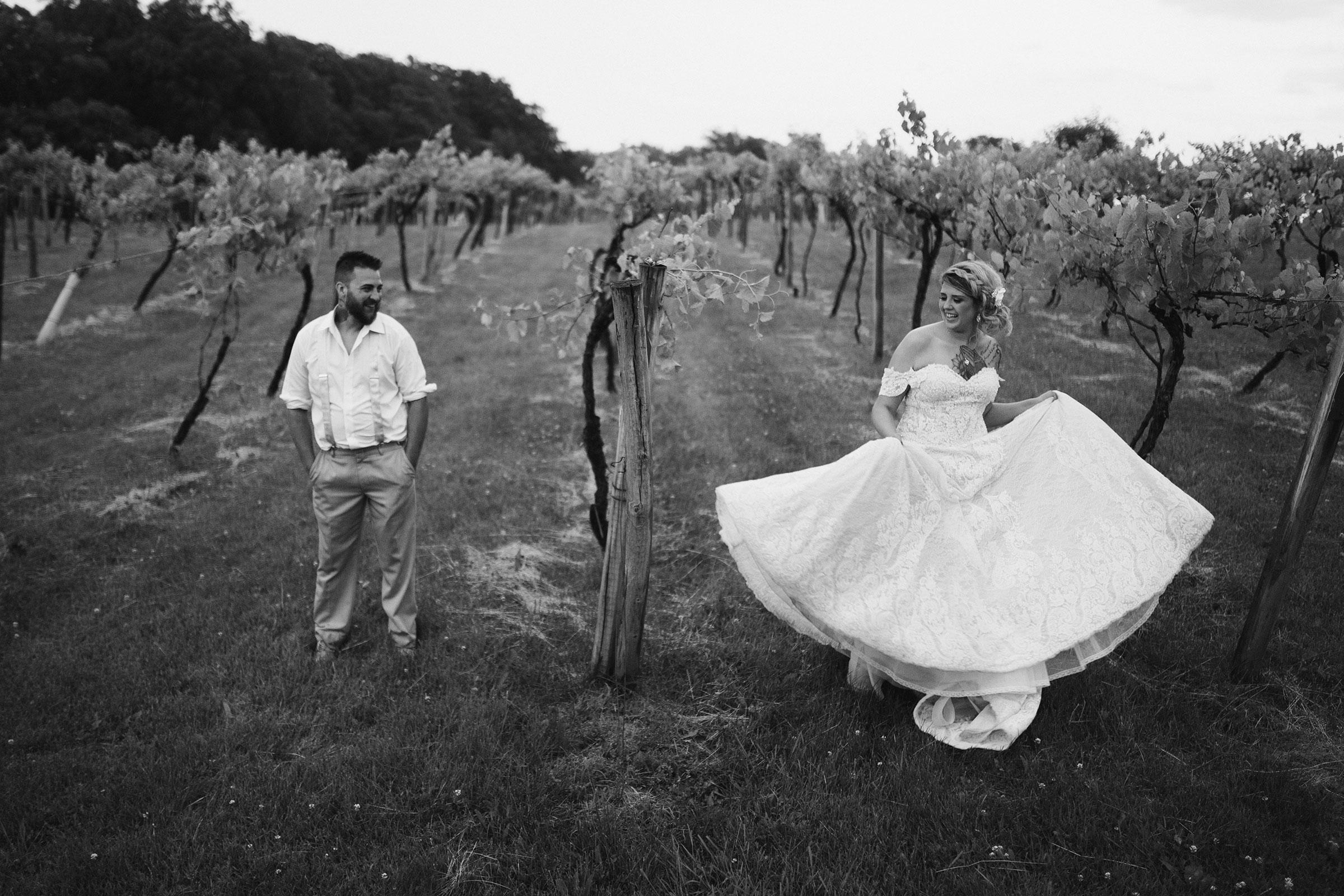 bride-twirling-dress-while-groom-watching-in-vineyard-wedding-summerset-winery-indianola-iowa-raelyn-ramey-photography.jpg