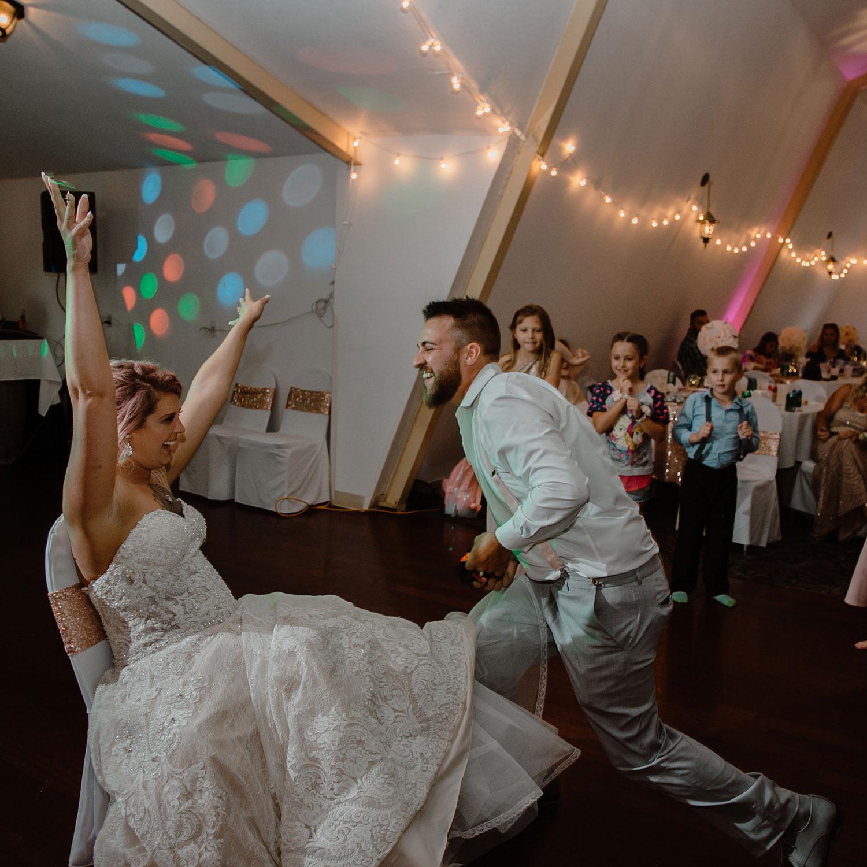 bride-yelling-after-groom-got-garter-off-wedding-summerset-winery-indianola-iowa-raelyn-ramey-photography.jpg