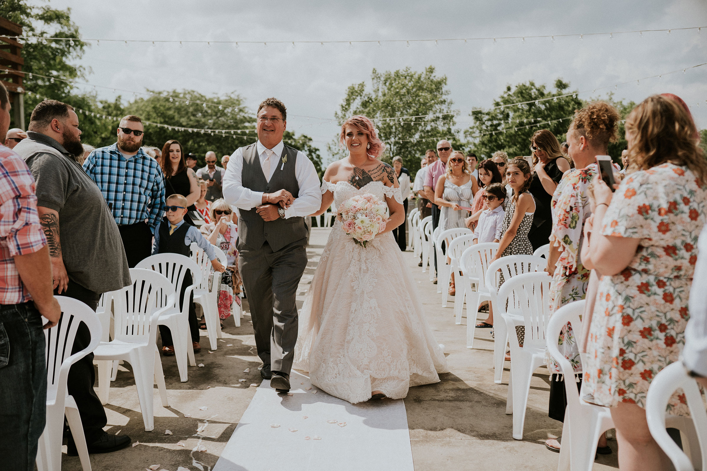 bride-walking-down-aisle-with-father-wedding-summerset-winery-indianola-iowa-raelyn-ramey-photography.jpg