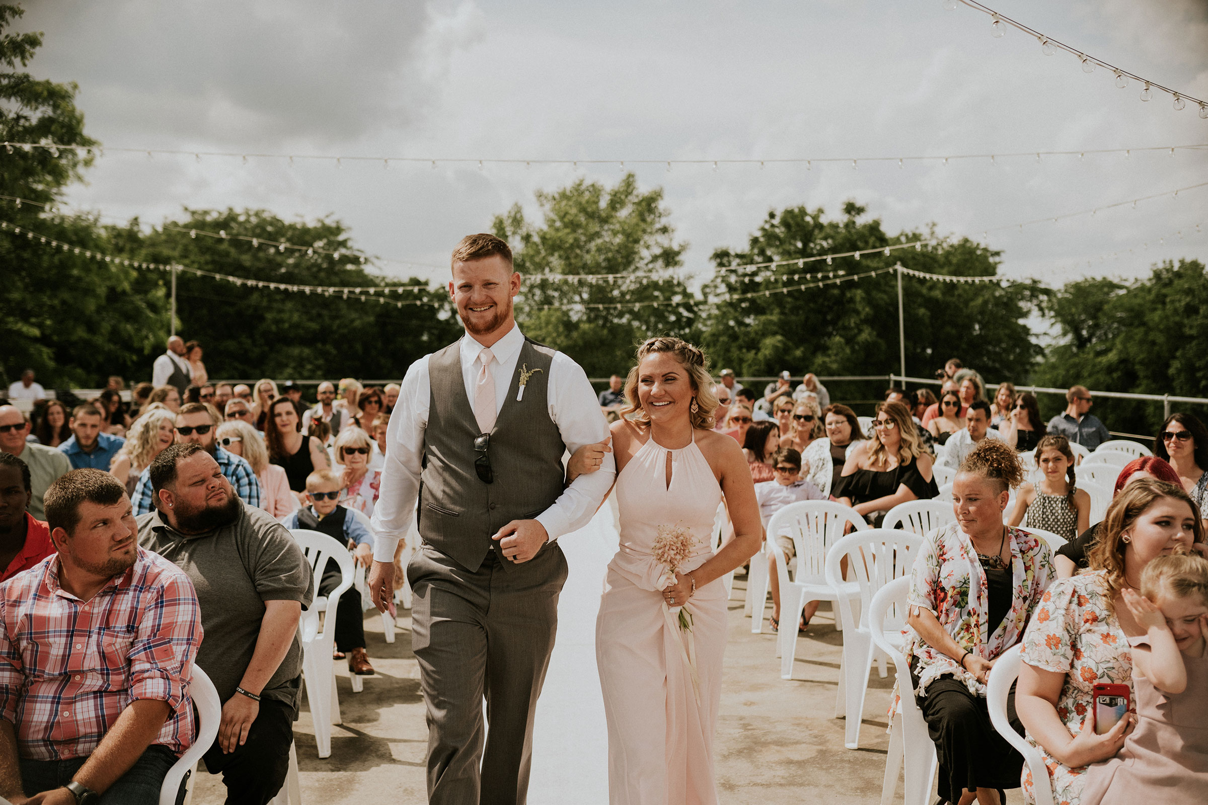 bridesmaid-and-groomsmen-walking-down-aisle-smiling-wedding-summerset-winery-indianola-iowa-raelyn-ramey-photography.jpg