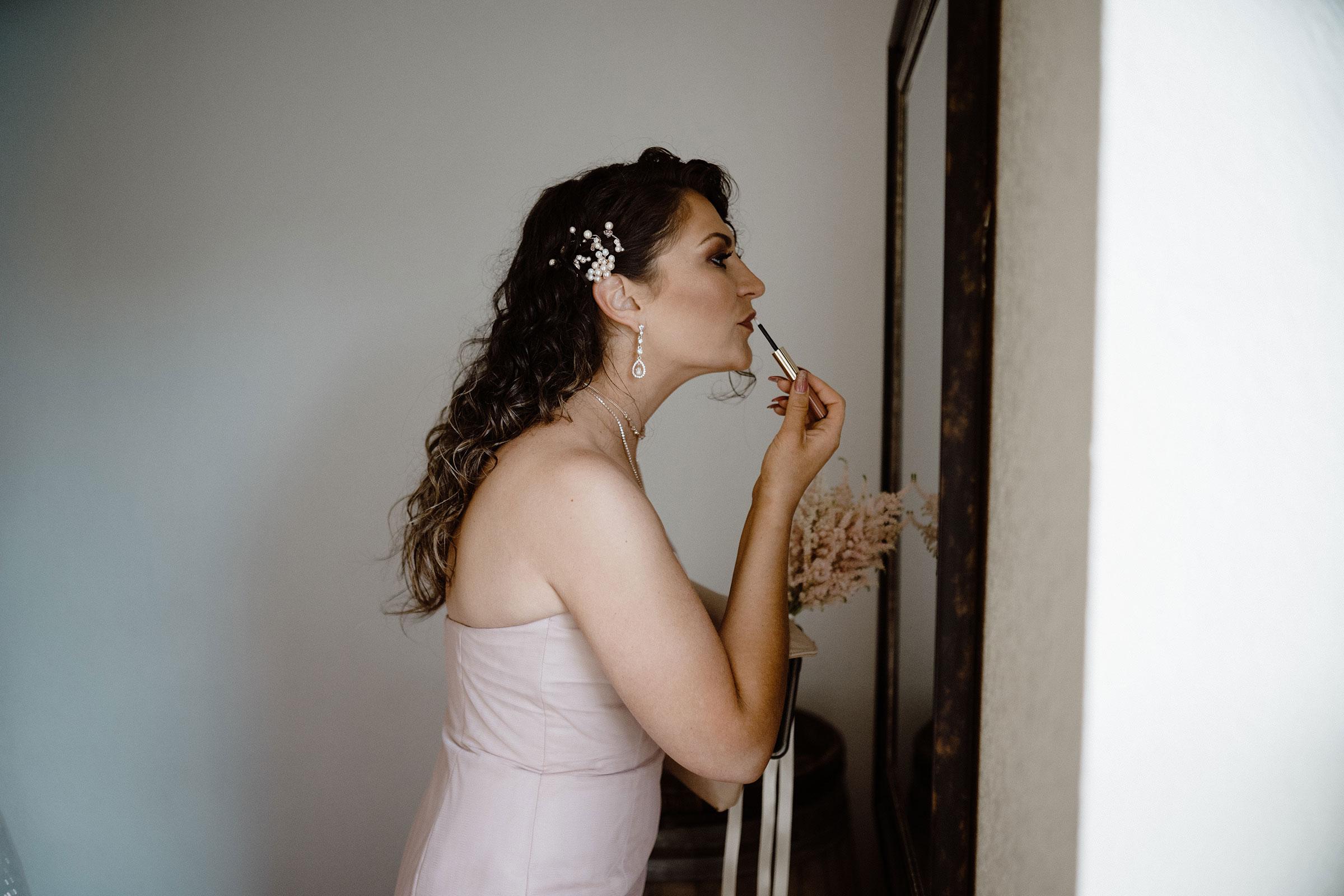 bridesmaid-putting-lipstick-on-wedding-summerset-winery-indianola-iowa-raelyn-ramey-photographyjpg