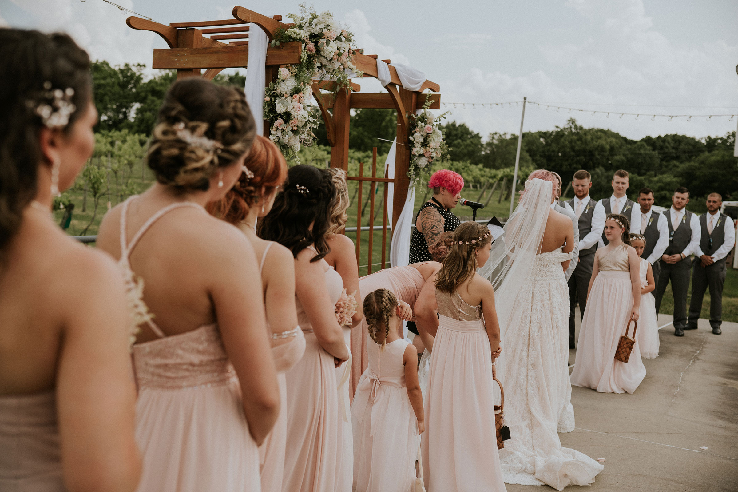bridesmaids-and-groomsmen-watching-couple-during-ceremony-summerset-winery-indianola-iowa-raelyn-ramey-photography.jpg
