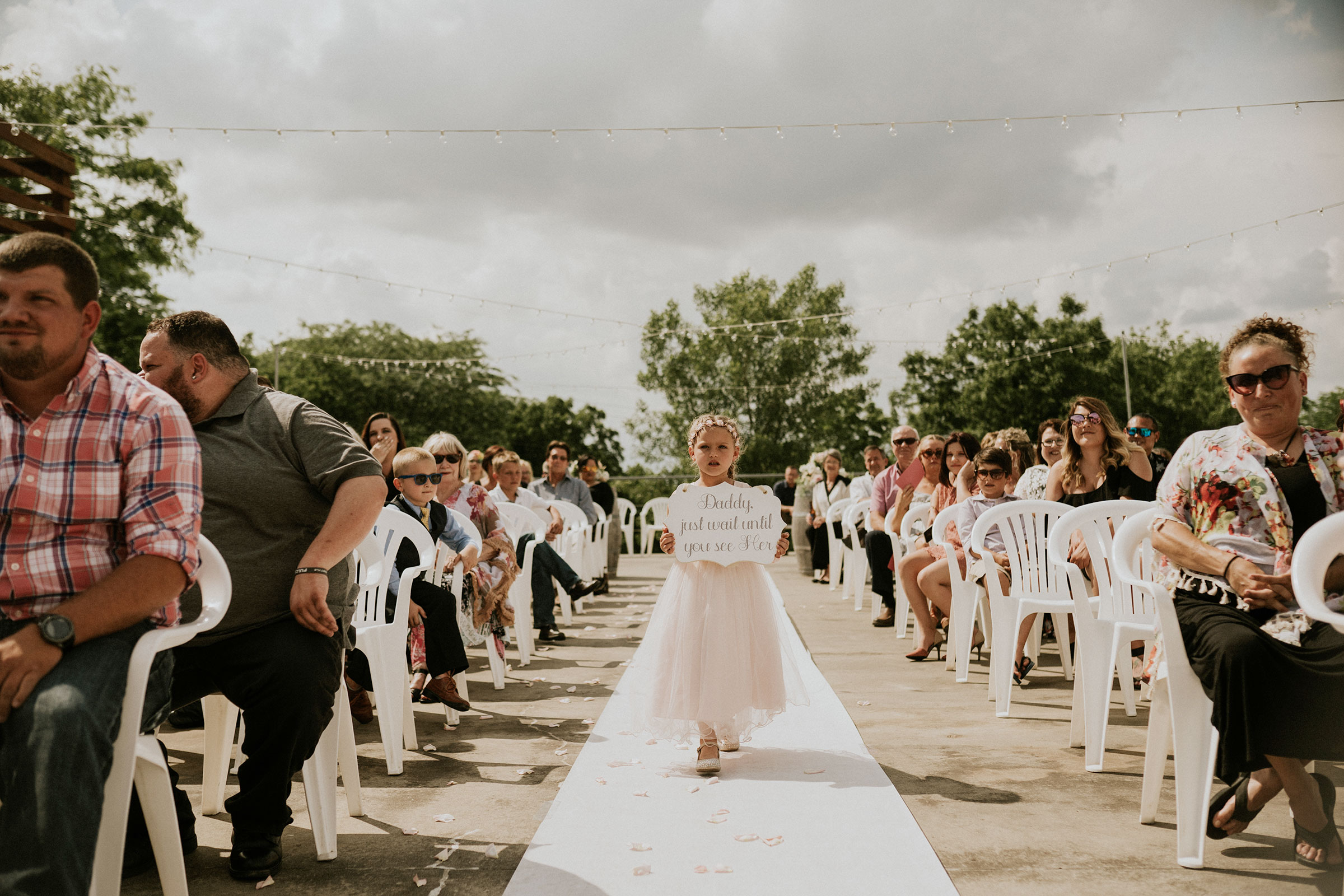 daughter-walking-down-aisle-with-sign-summerset-winery-indianola-iowa-raelyn-ramey-photography.jpg