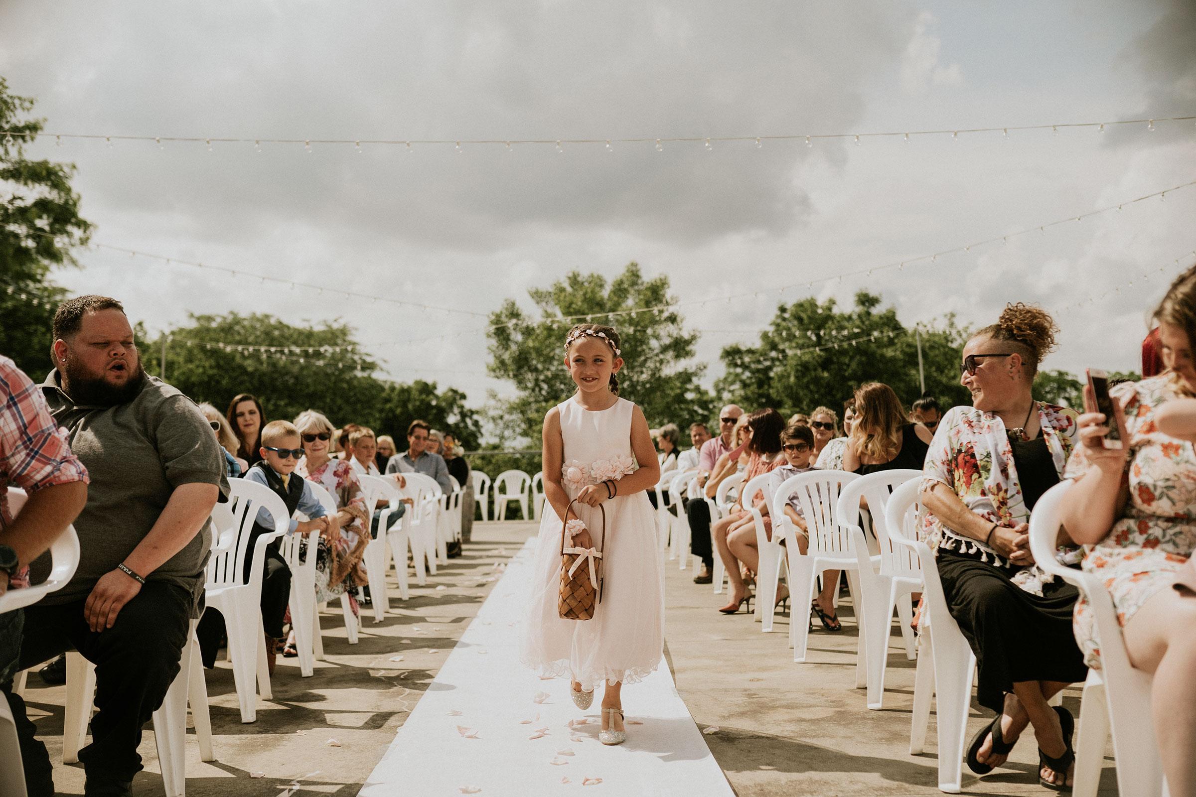 flower-girl-walking-down-aisle-wedding-summerset-winery-indianola-iowa-raelyn-ramey-photography.jpg