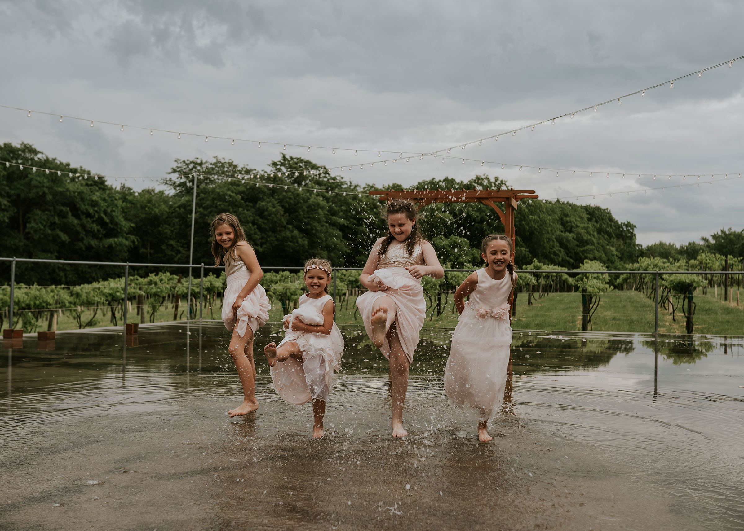 flower-girls-playing-in-rain-kicking-puddles-wedding-summerset-winery-indianola-iowa-raelyn-ramey-photography.jpg