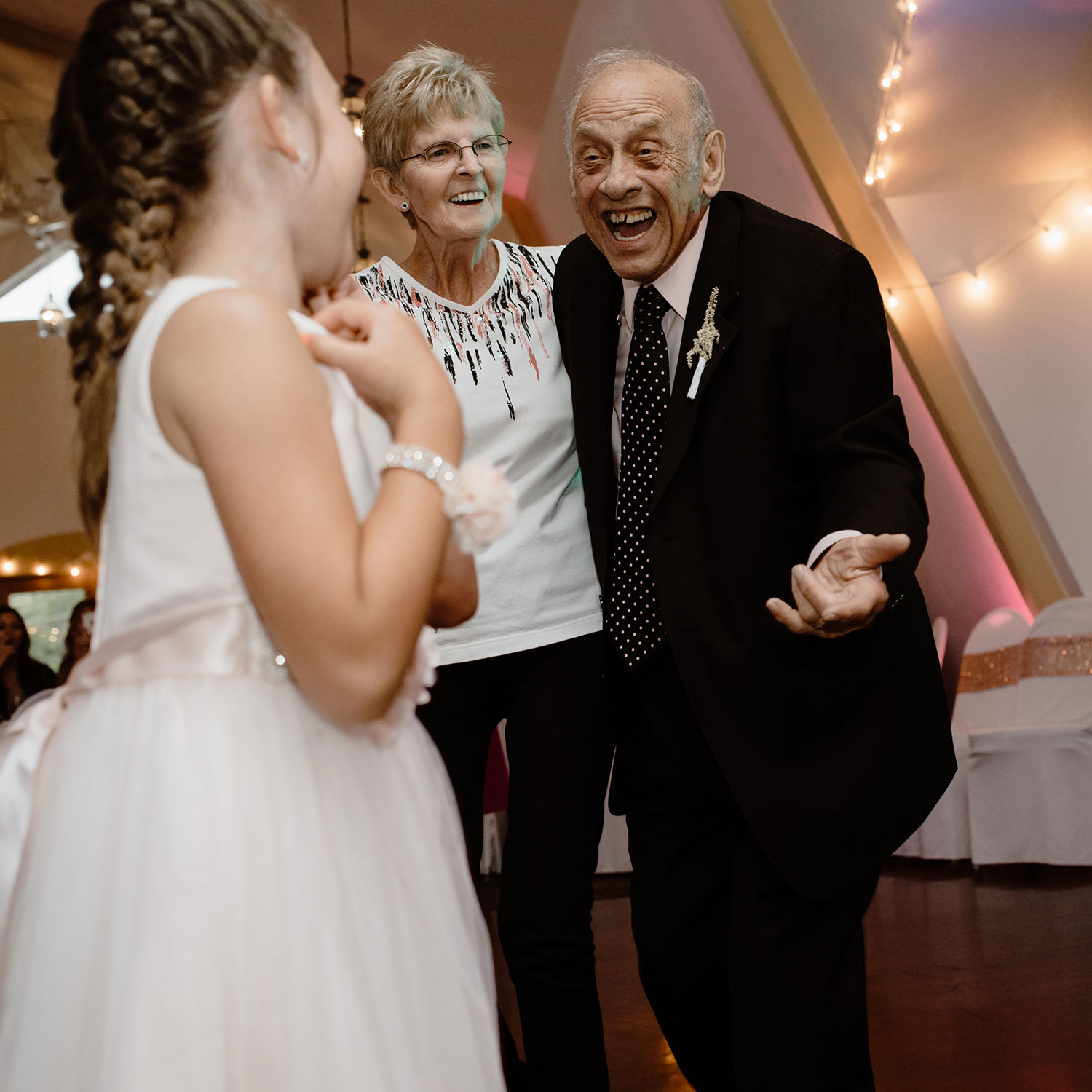 grandparents-laughing-to-get-child-to-dance-wedding-summerset-winery-indianola-iowa-raelyn-ramey-photography.jpg