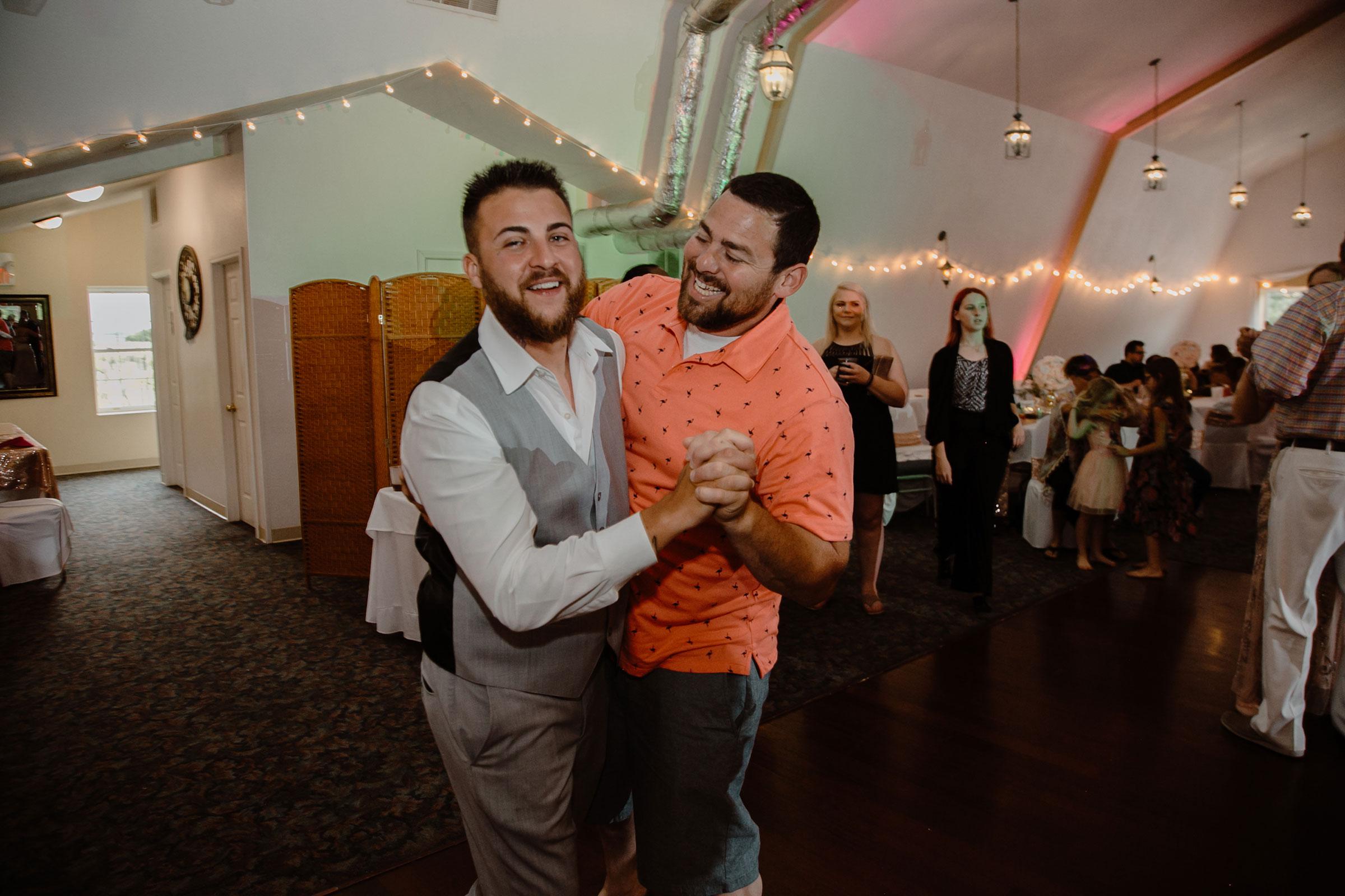 groom-dancing-with-friend-wedding-summerset-winery-indianola-iowa-raelyn-ramey-photography.jpg