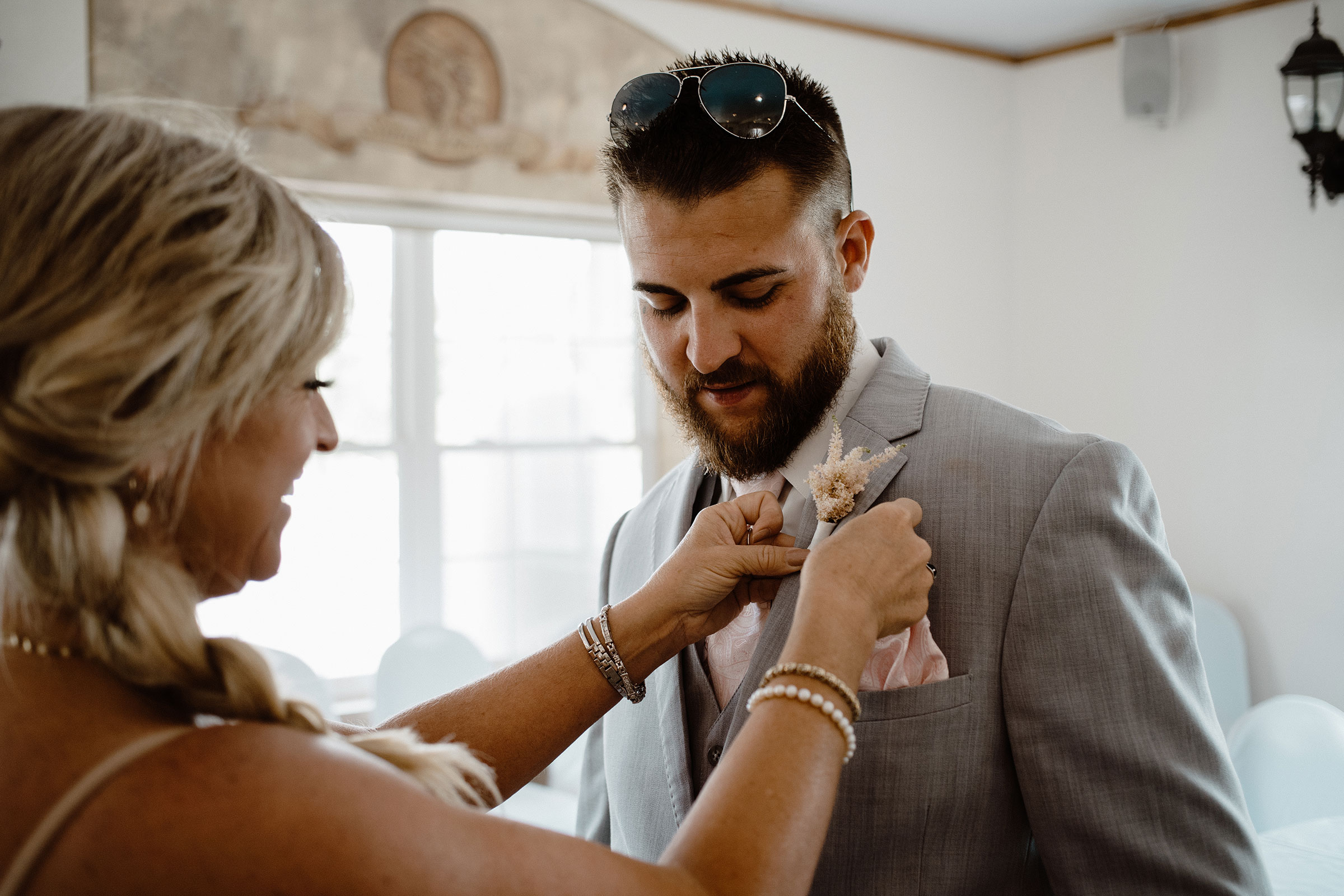 groom-getting-flowers-from-mom-wedding-summerset-winery-indianola-iowa-raelyn-ramey-photography.jpg