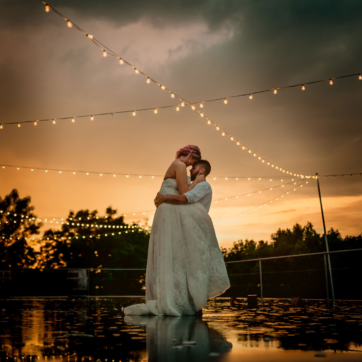 groom-holding-bride-in-arms-in-rain-under-twinkling-lights-wedding-summerset-winery-indianola-iowa-raelyn-ramey-photography.jpg