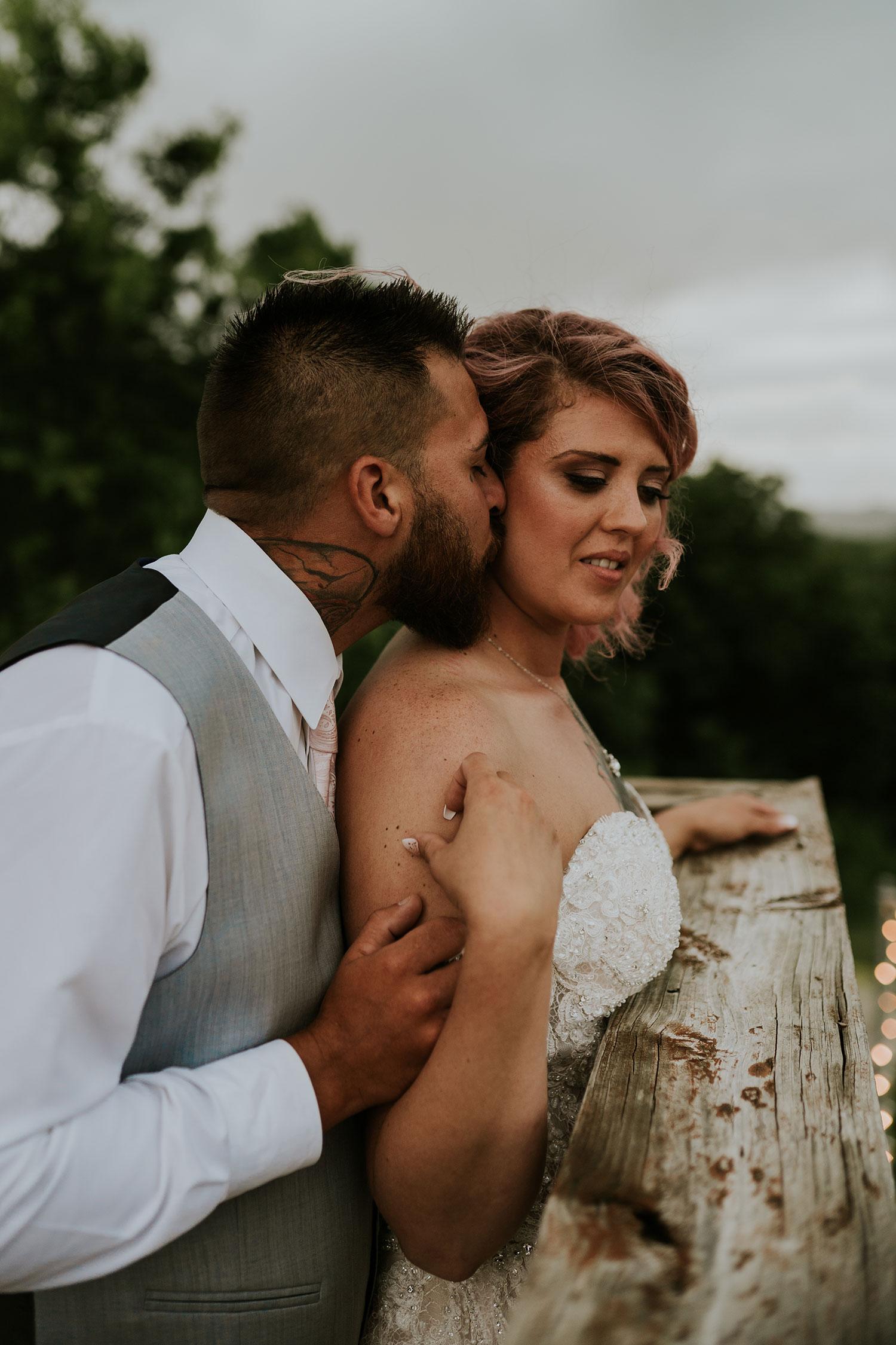 groom-kissing-bride-on-cheek-wedding-summerset-winery-indianola-iowa-raelyn-ramey-photography.jpg