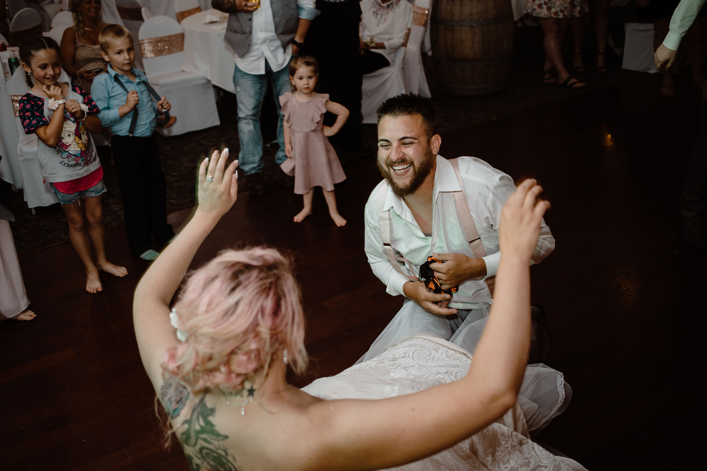groom-laughing-after-getting-garter-wedding-summerset-winery-indianola-iowa-raelyn-ramey-photography.jpg