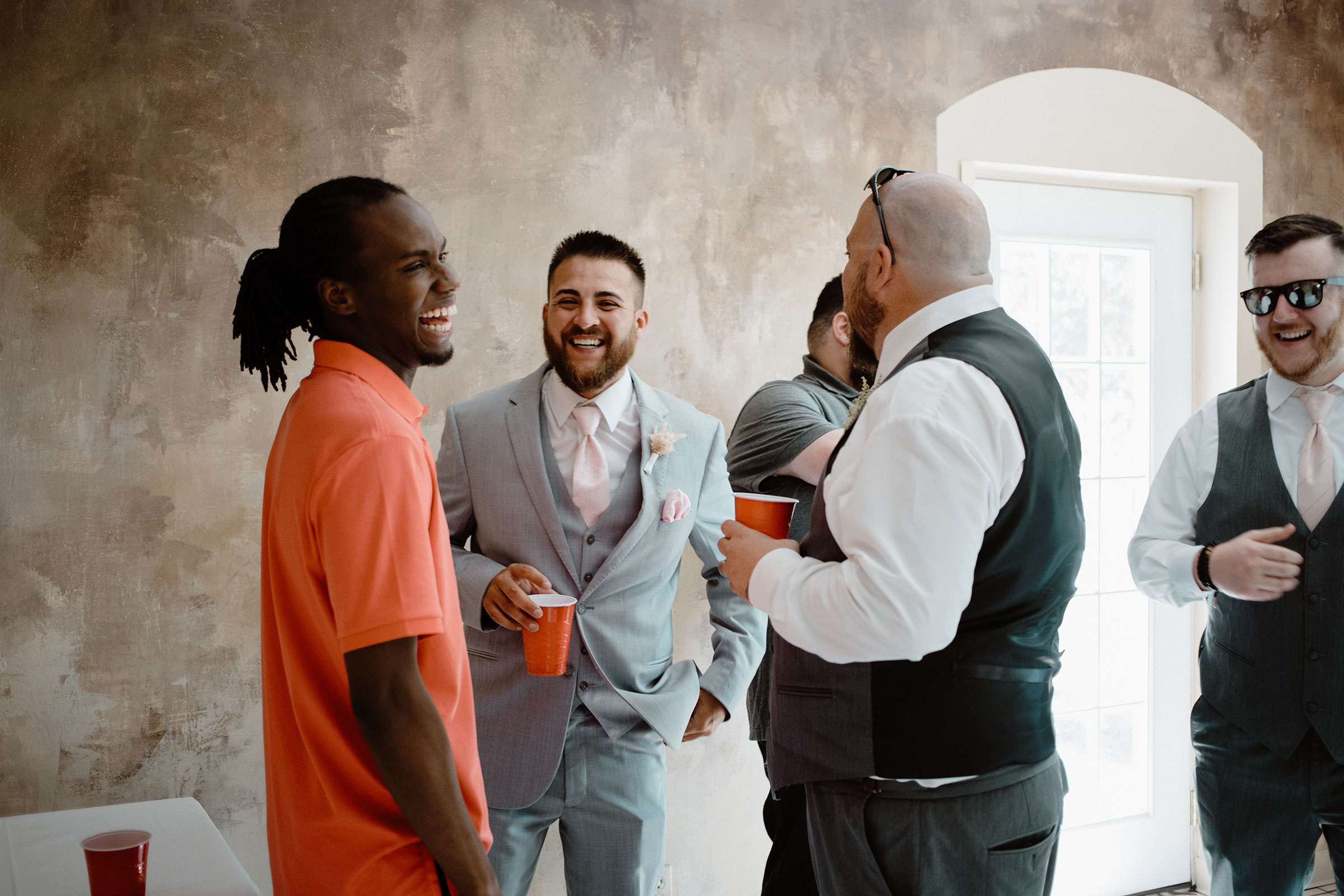 groom-lauhging-and-talking-with-guests-wedding-summerset-winery-indianola-iowa-raelyn-ramey-photography.jpg
