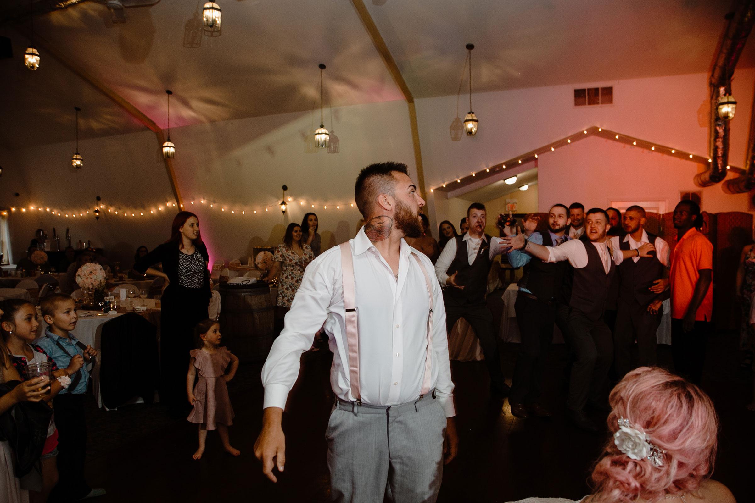 groom-tossing-garter-wedding-summerset-winery-indianola-iowa-raelyn-ramey-photography.jpg