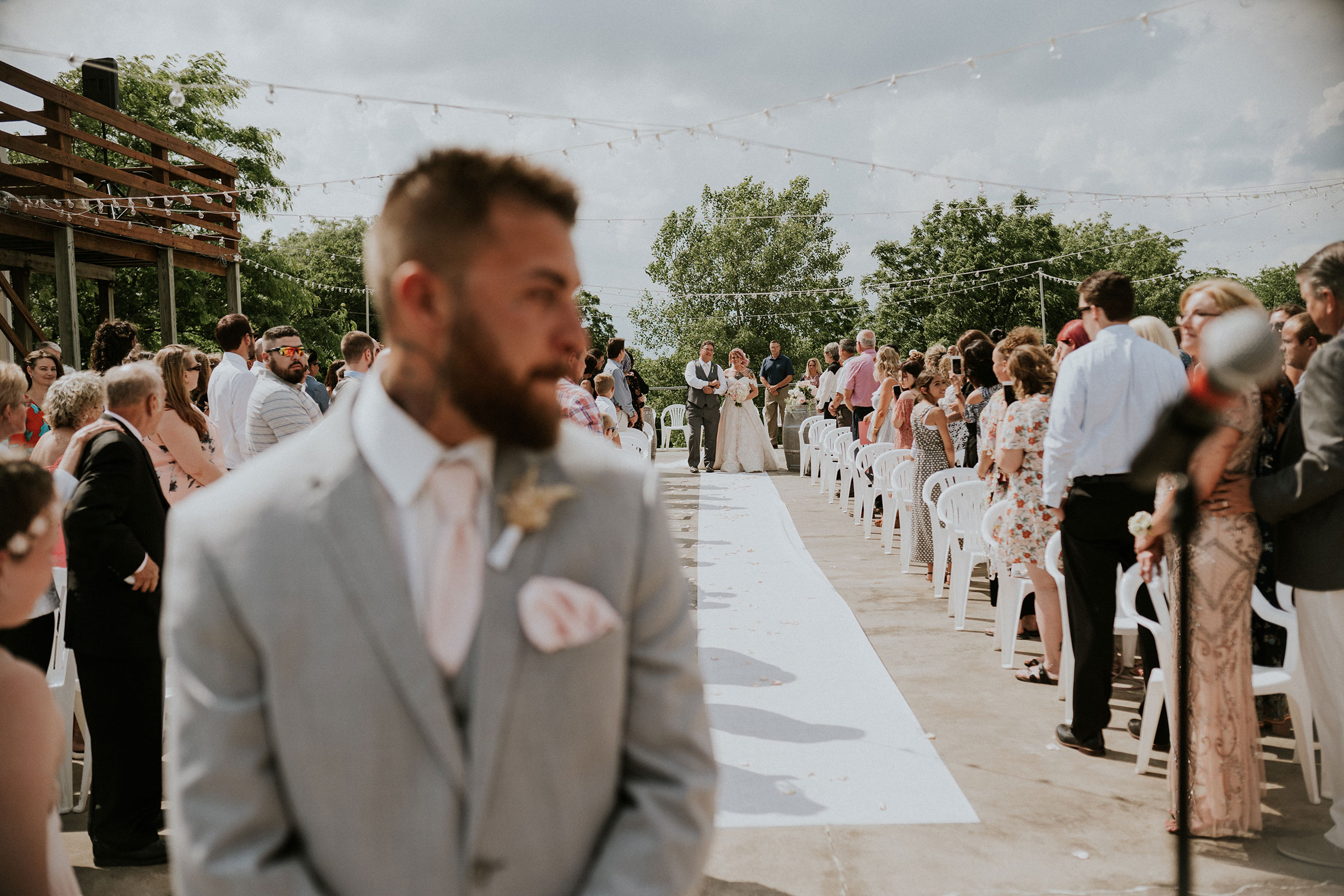 groom-turned-away-from-bride-as-she-walks-down-aisle-wedding-summerset-winery-indianola-iowa-raelyn-ramey-photography.jpg