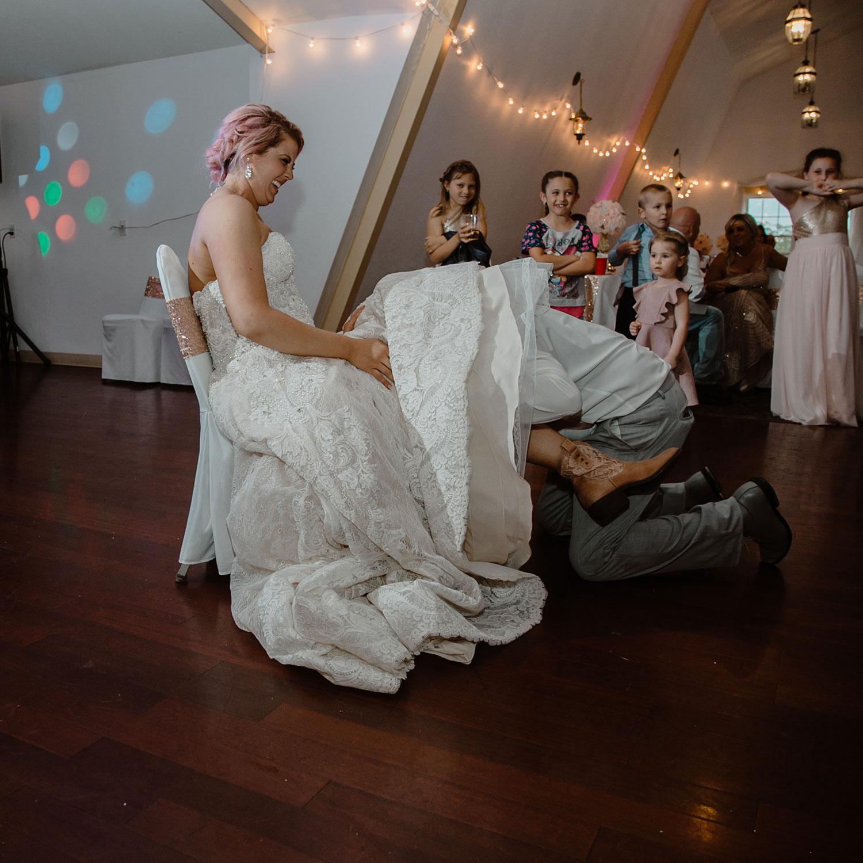groom-under-dress-getting-garter-wedding-summerset-winery-indianola-iowa-raelyn-ramey-photography.jpg