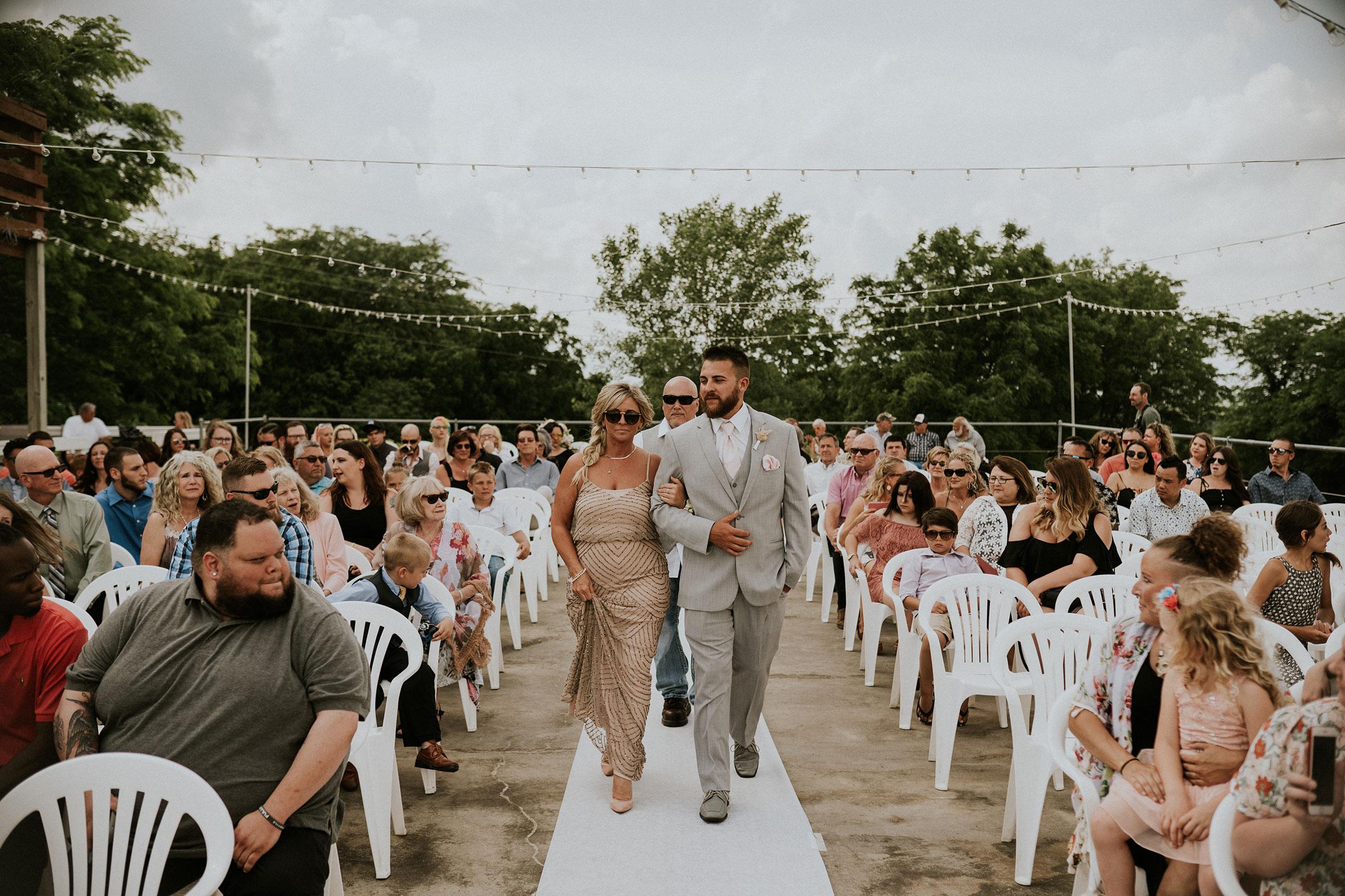 groom-walking-mother-down-aisle-wedding-summerset-winery-indianola-iowa-raelyn-ramey-photography.jpg