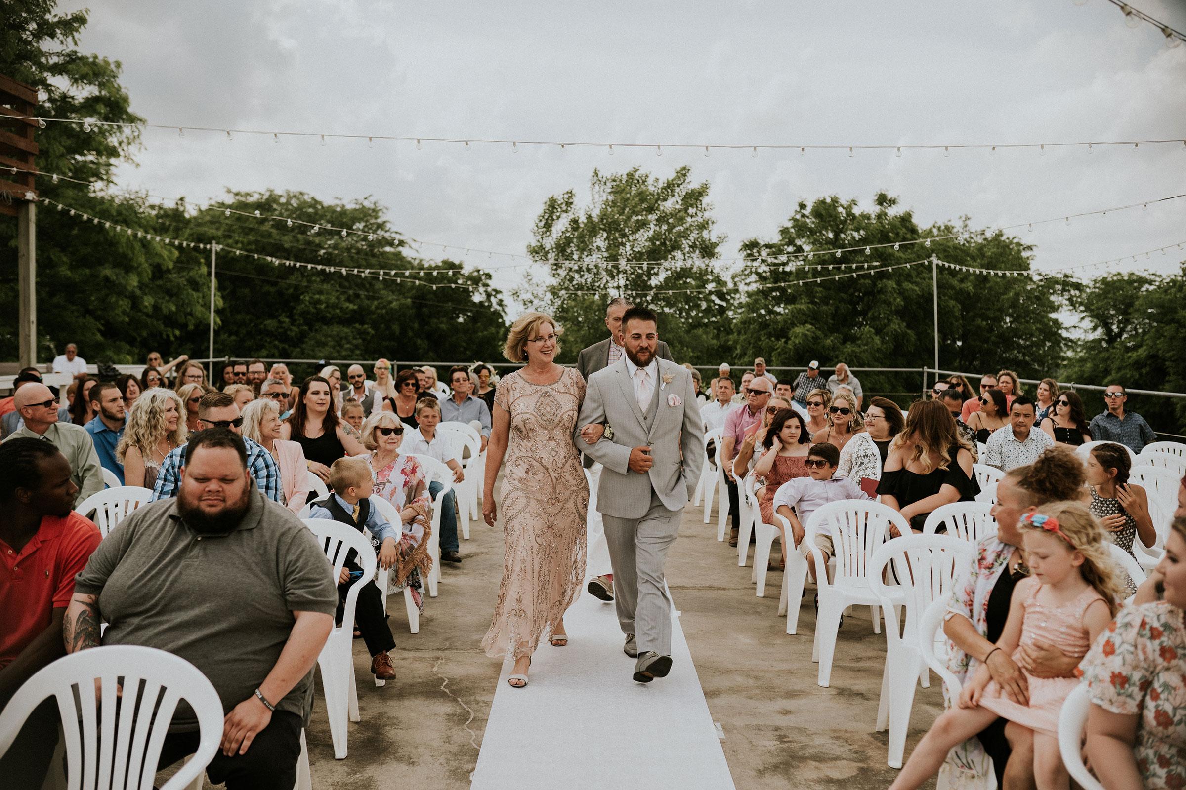 groom-walking-mother-of-bride-down-aisle-wedding-summerset-winery-indianola-iowa-raelyn-ramey-photography.jpg