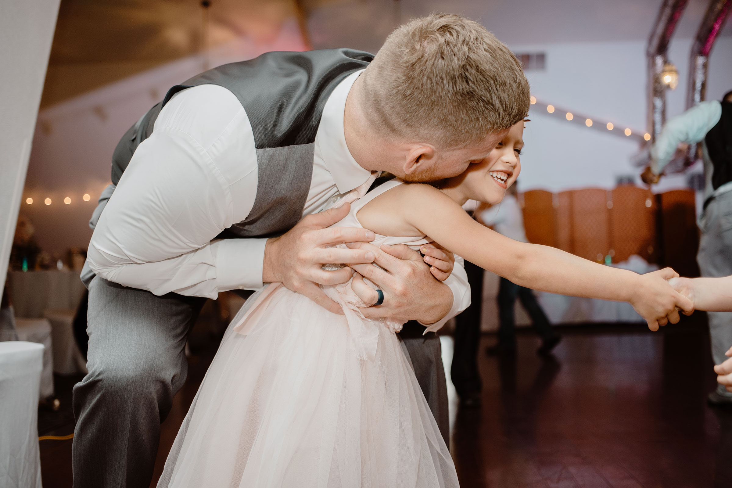 groomsmen-loving-on-flower-girl-wedding-summerset-winery-indianola-iowa-raelyn-ramey-photography.jpg