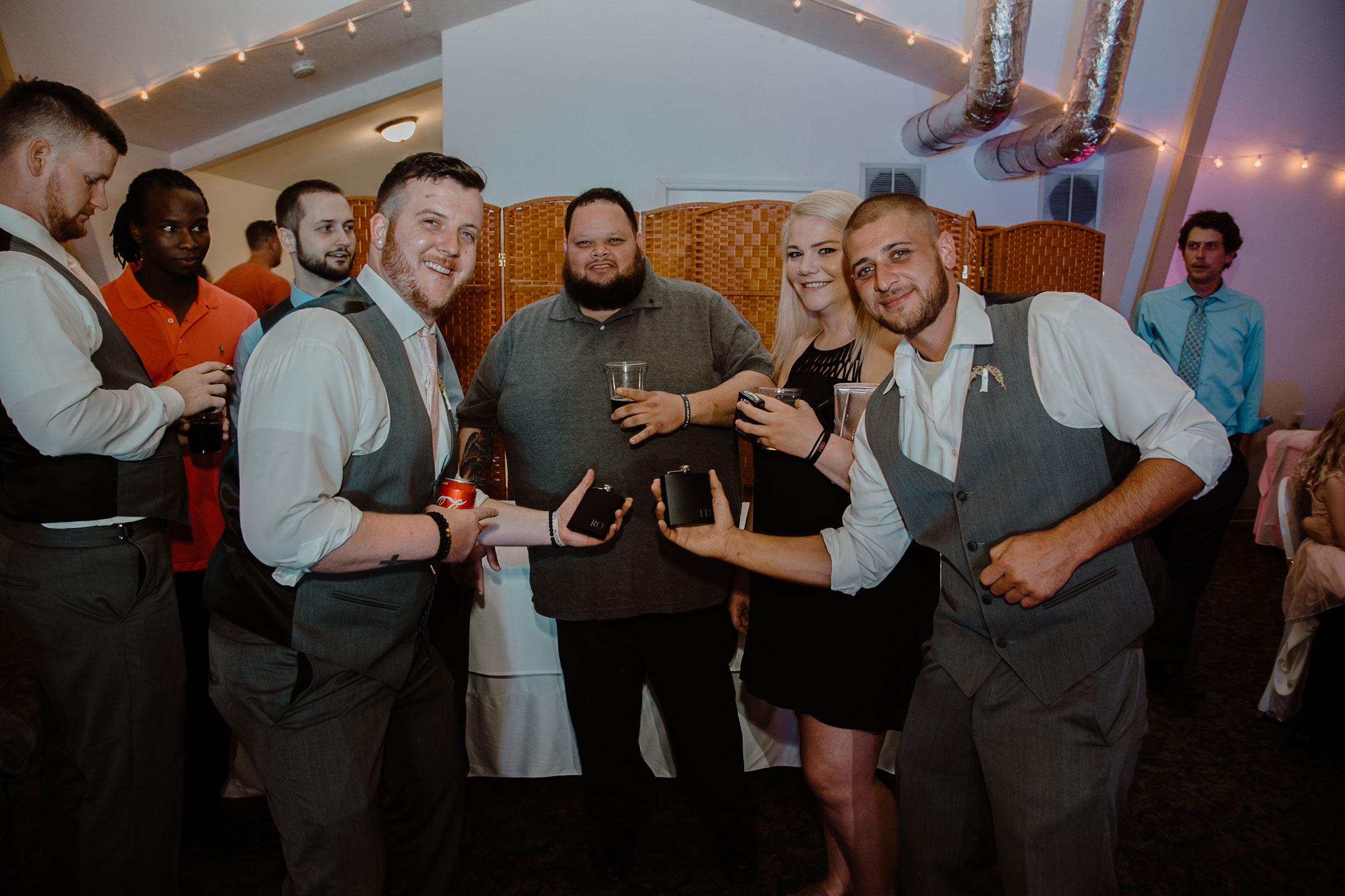 groomsmen-posing-with-flasks-wedding-summerset-winery-indianola-iowa-raelyn-ramey-photography.jpg