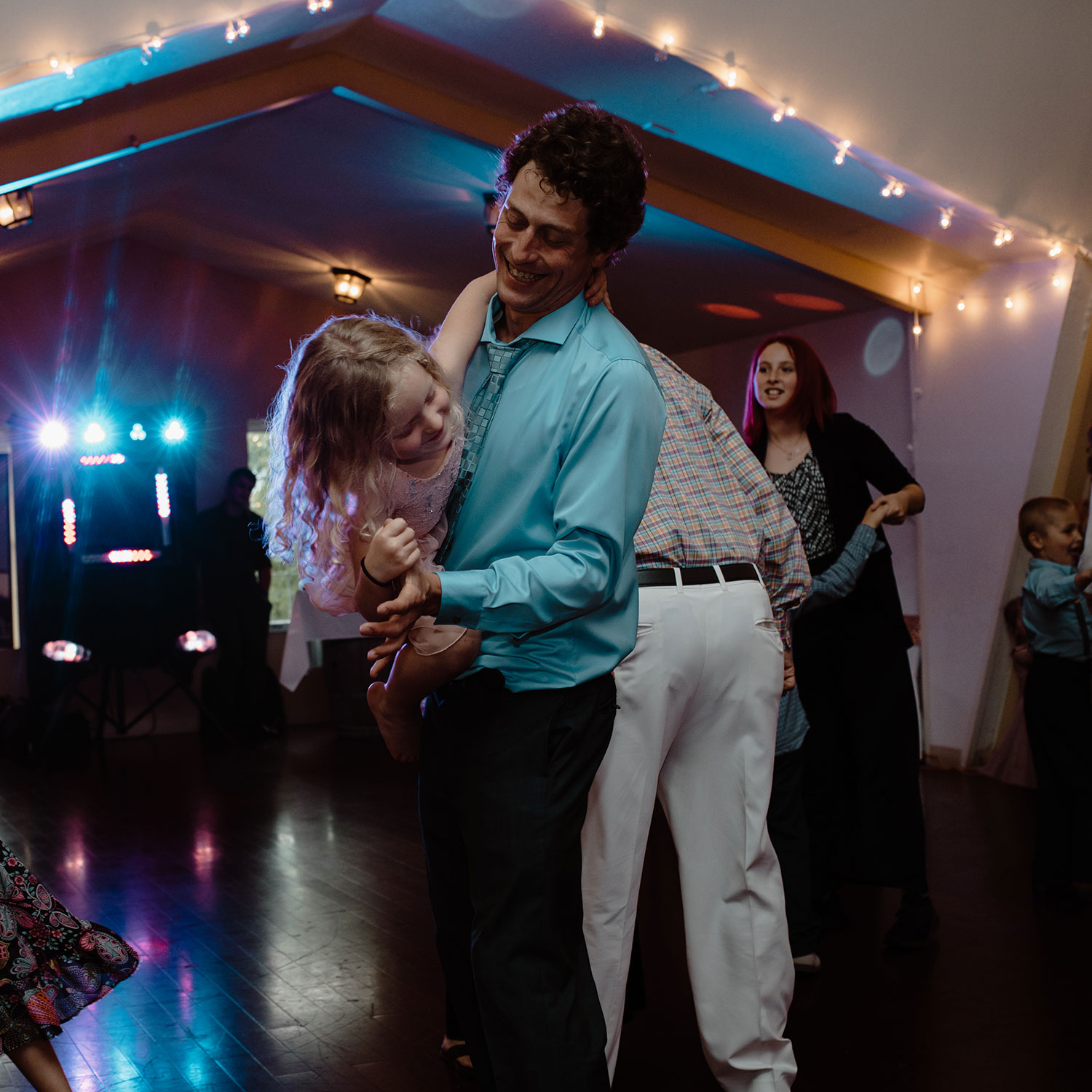 guest-dancing-with-child-wedding-summerset-winery-indianola-iowa-raelyn-ramey-photography.jpg