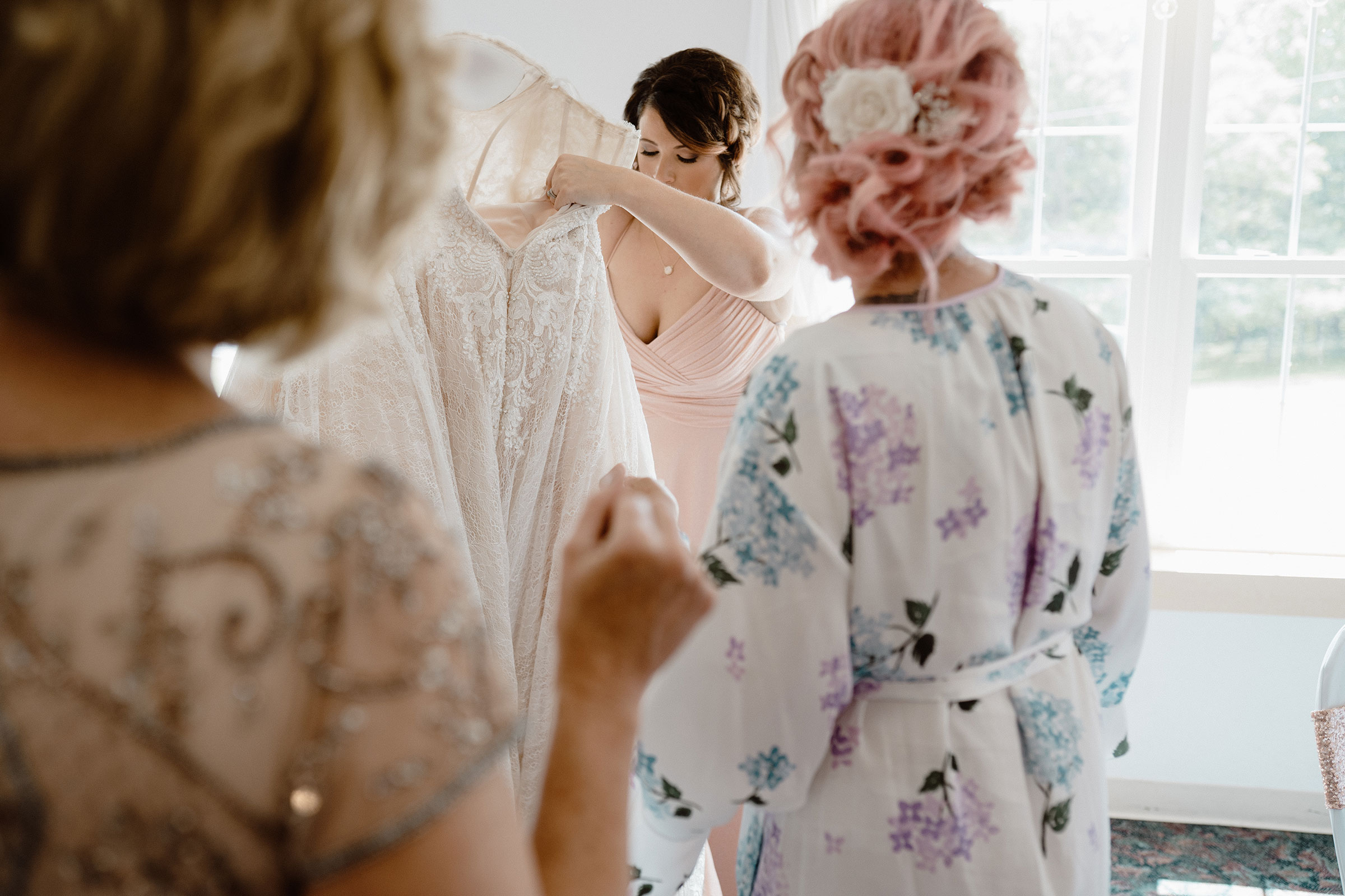 sister-getting-dress-ready-for-bride-wedding-summerset-winery-indianola-iowa-raelyn-ramey-photography.jpg
