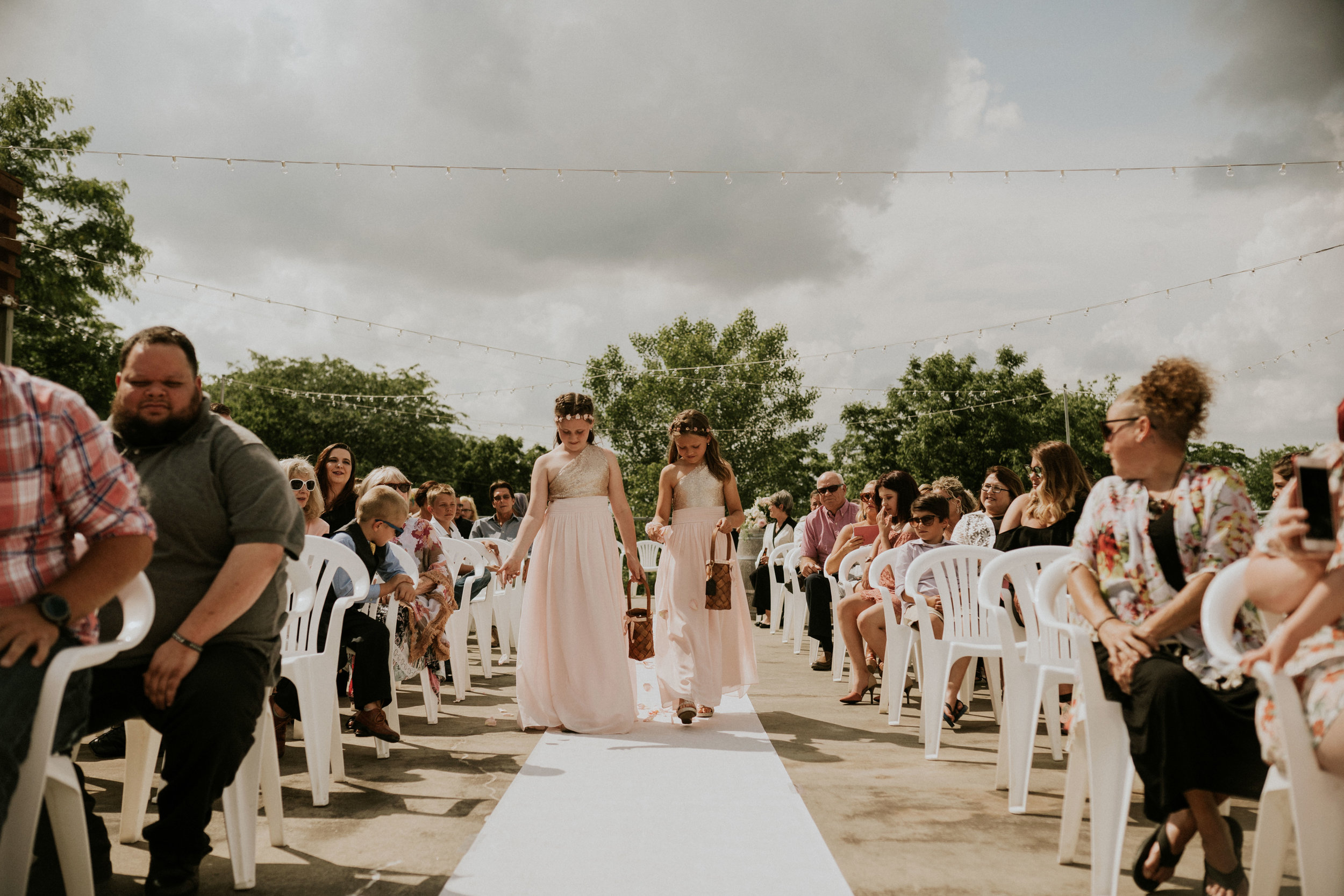 two-flower-girls-walking-down-aisle-wedding-summerset-winery-indianola-iowa-raelyn-ramey-photography.jpg