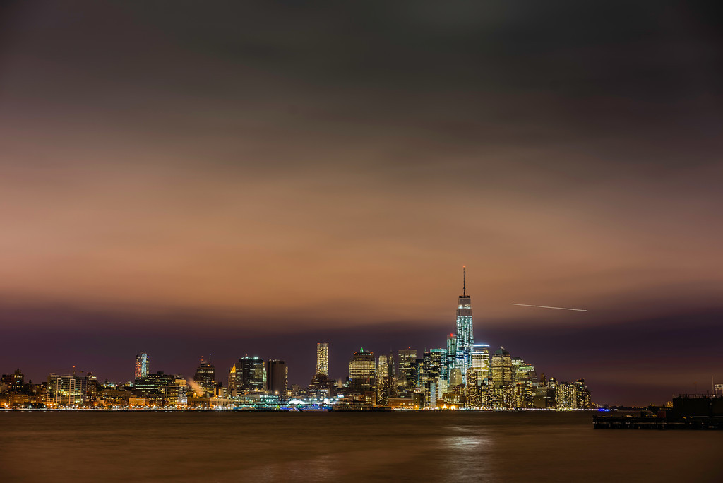 Taken from Hoboken, NJ.  An airplane in the distance behind One World Trade Center (looks like a shooting star).