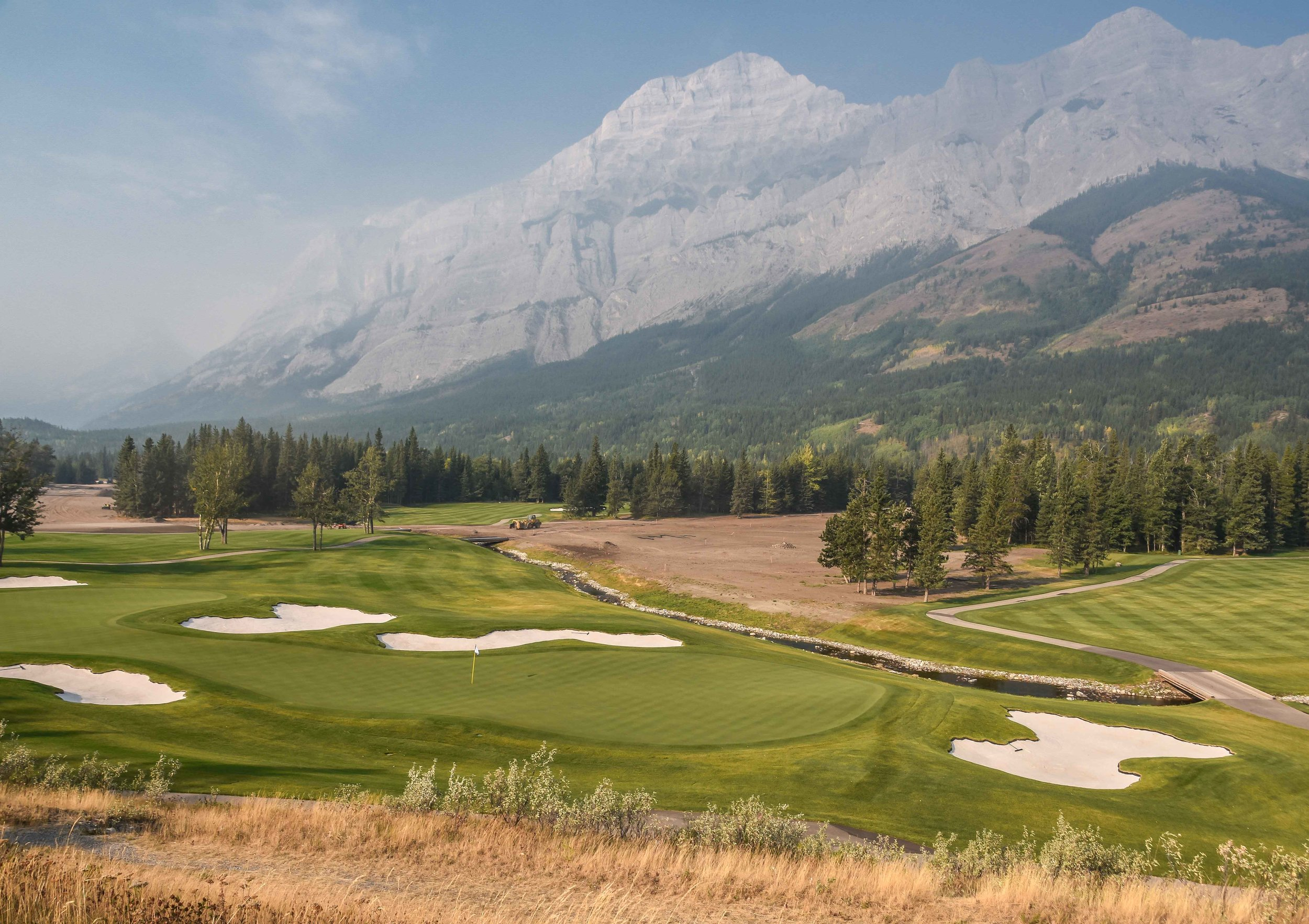 The dual green on the Mt Lorette 18.  You can see the 9th hole on the Mt Kidd 18 still under construction below the mountains.