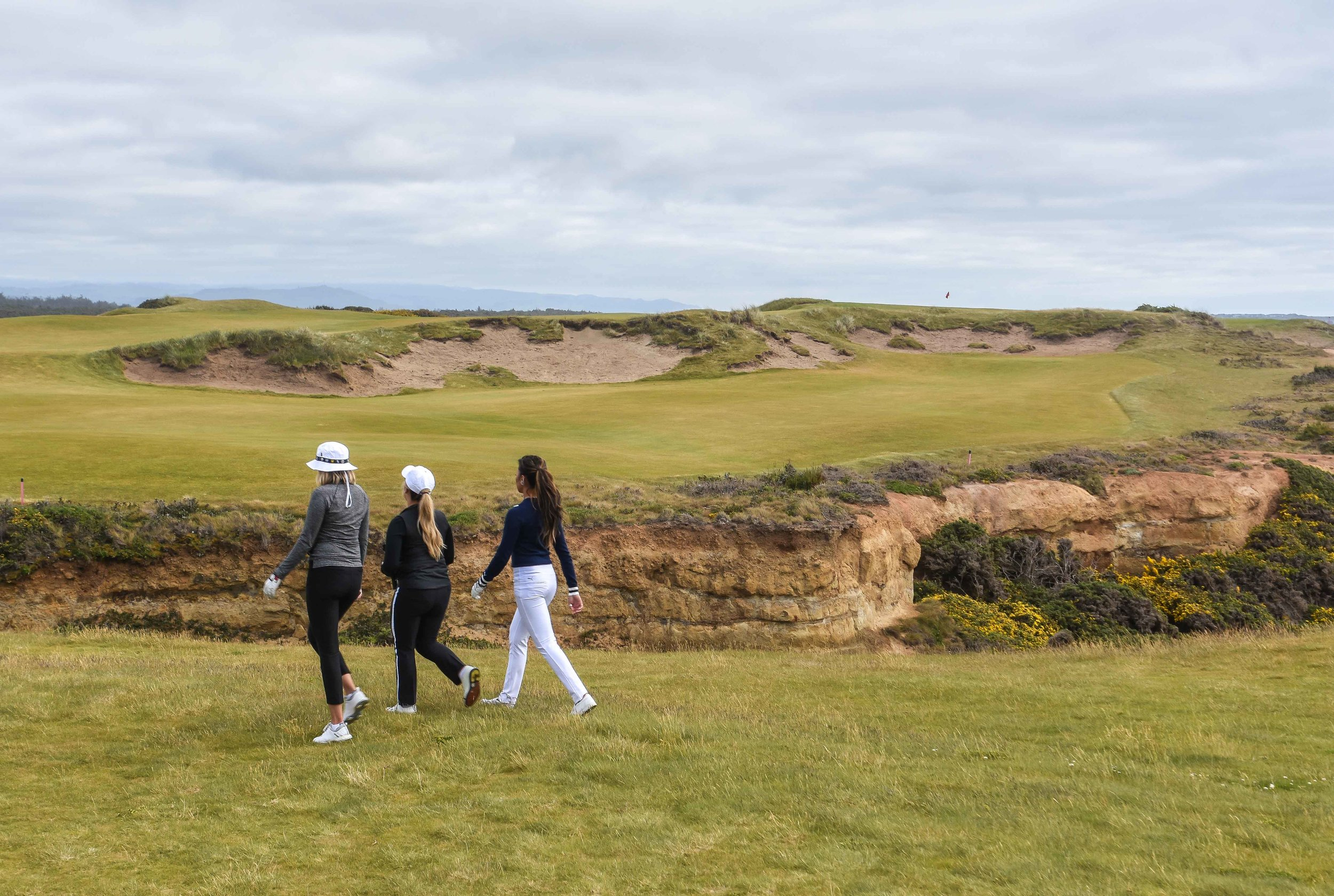 Nikki, Chelsea, and Tisha stroll hard on the 16th at Bandon Dunes.