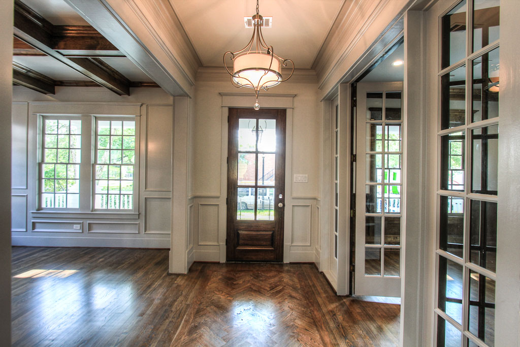 The sunny foyer captures the high level of finishing and detail found throughout the home: paneled wall details, cherrywood herringbone inlay in the reclaimed hardwood floors, and custom casing on all doorways and windows.