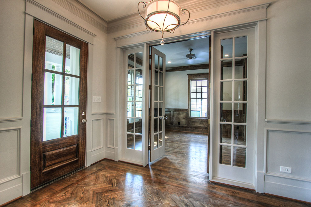 Another view of the foyer, looking into the richly hued study through divided light French doors and sidelights.